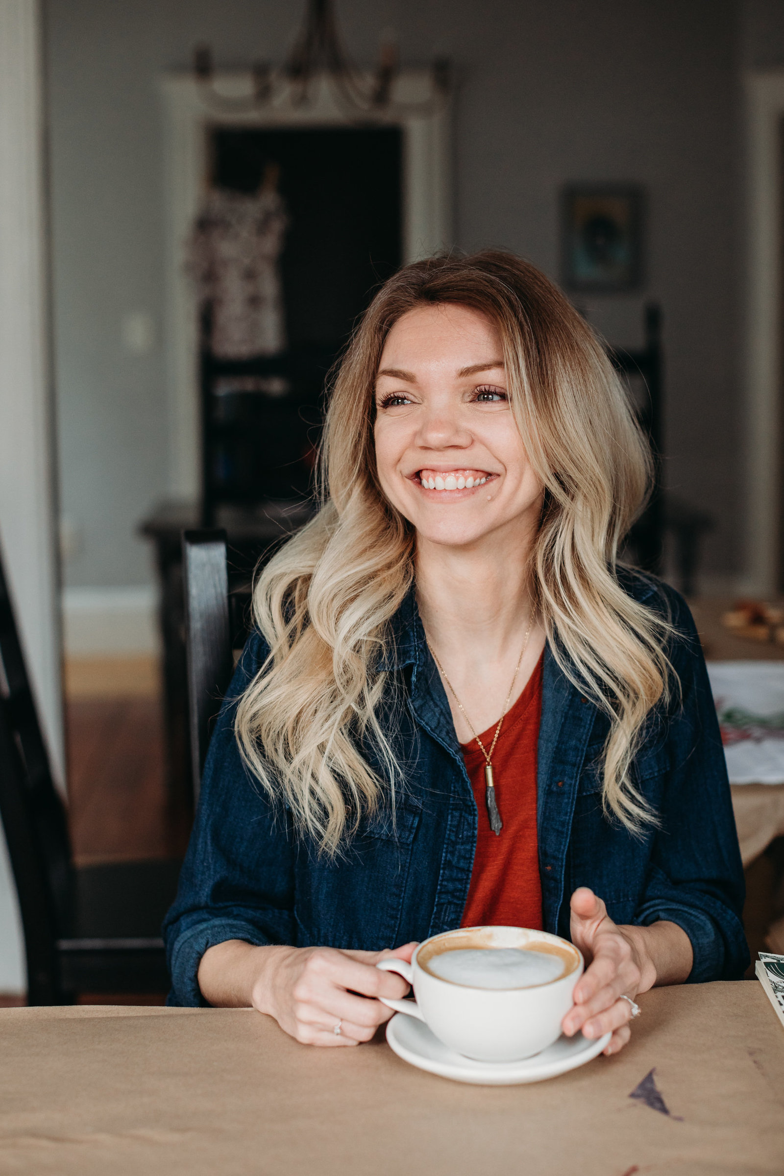woman with latte smiles in home studio