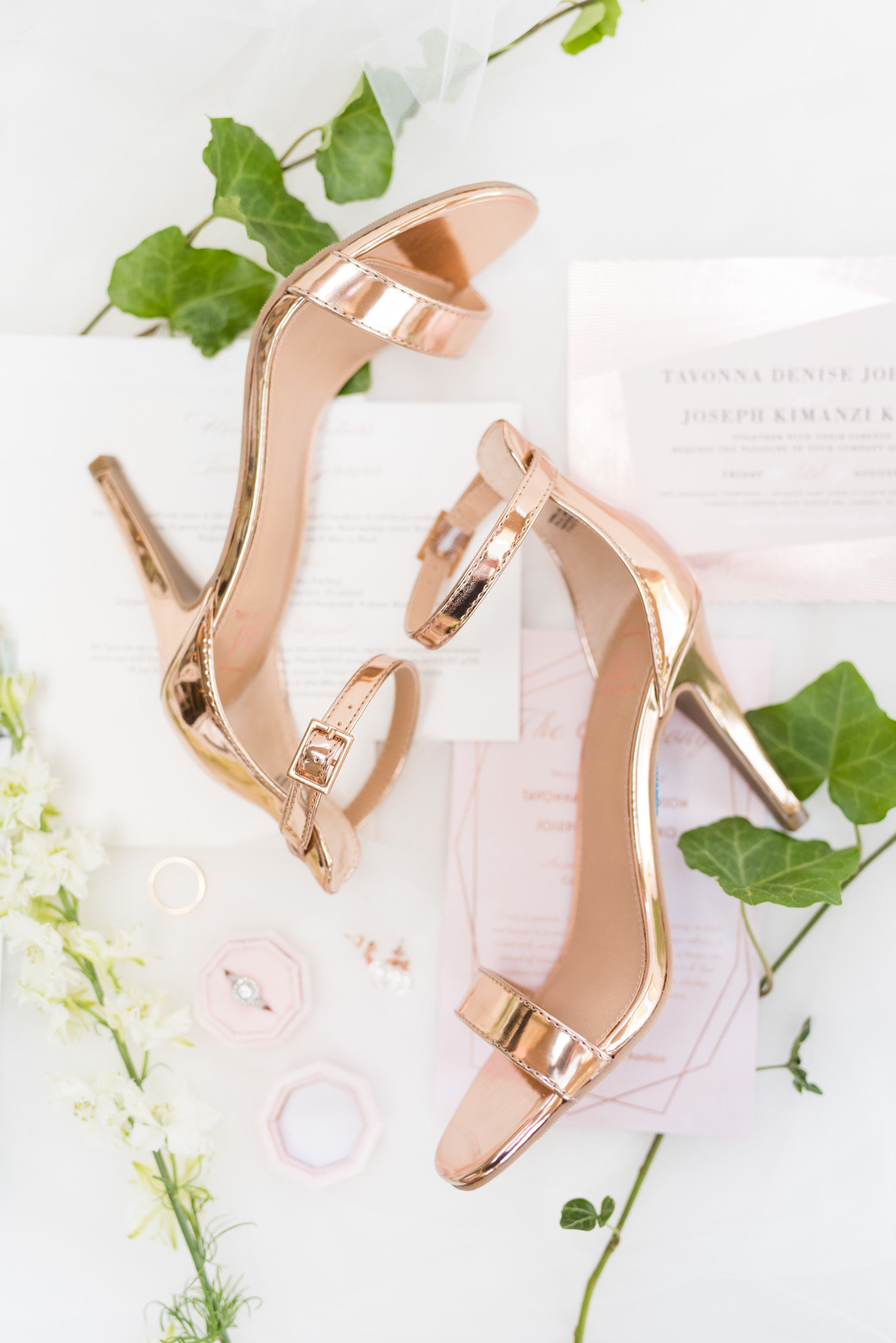Bride's shoes sit on invitation suite.