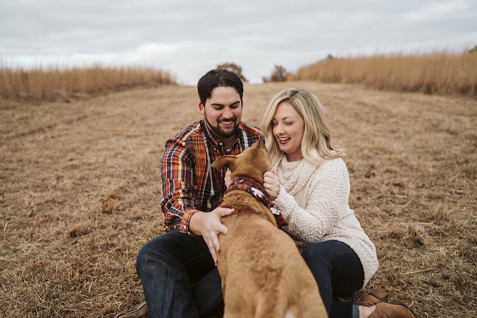 engaged couple plays with their dog at shawnee mission park