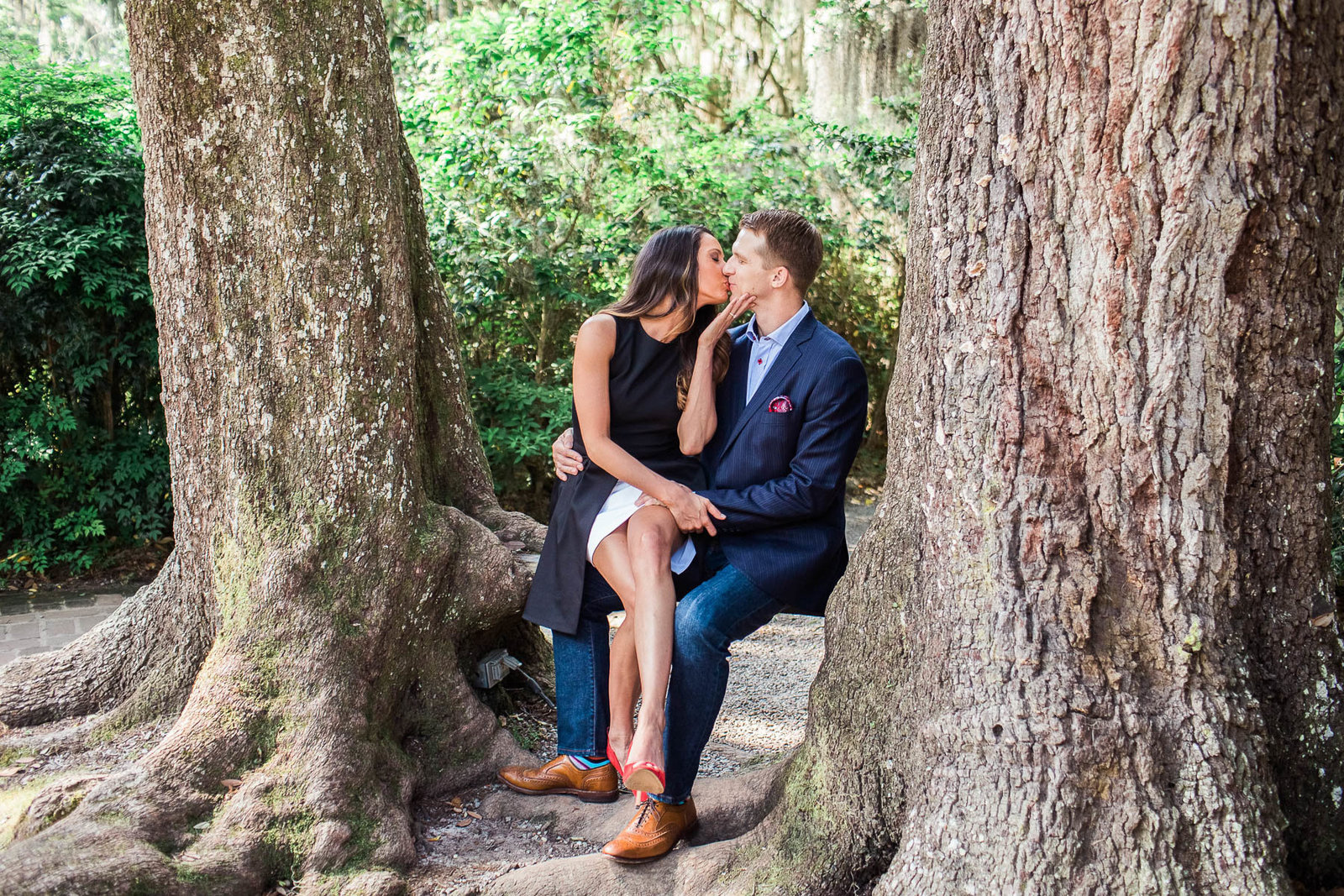 Engaged couple sit on a natural bench between two trees, Magnolia Plantation, Charleston, South Carolina