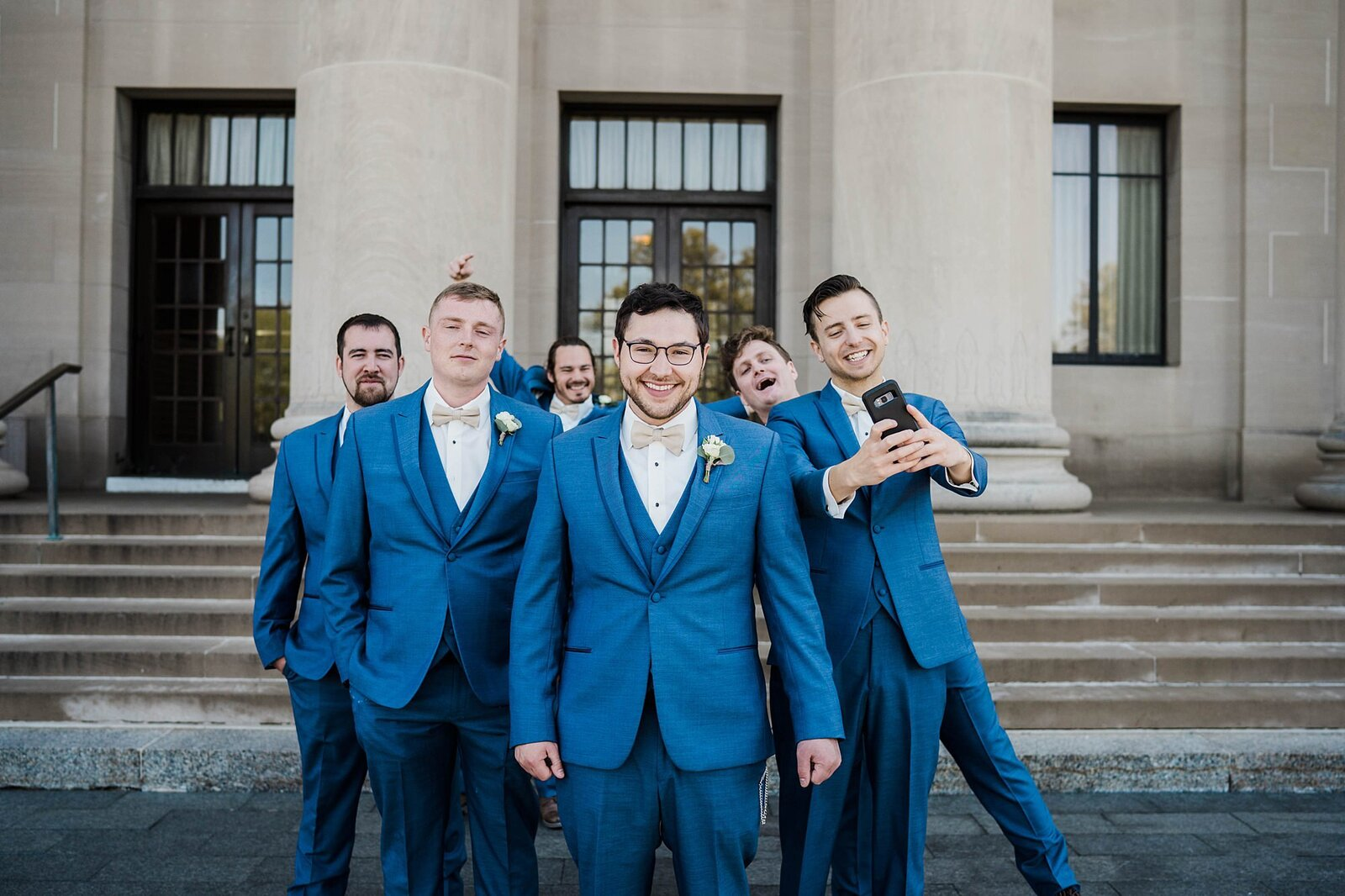 Groom and his groomsmen take a selfie in front of the nelson atkins
