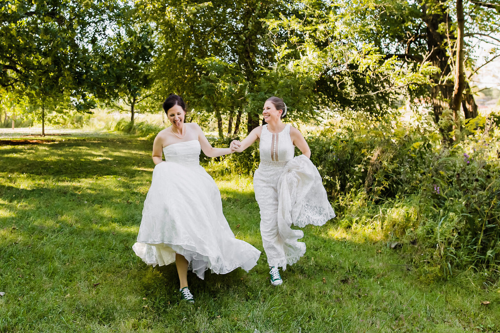 LGBT couple holding hands running at their St. Louis wedding in Forest Park