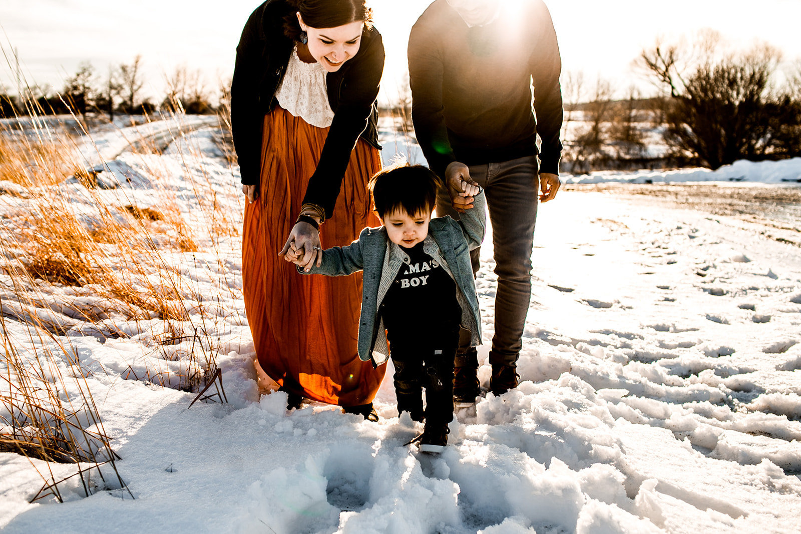 Des Moines Iowa lifestyle family photograph in winter. Child walking with parents.