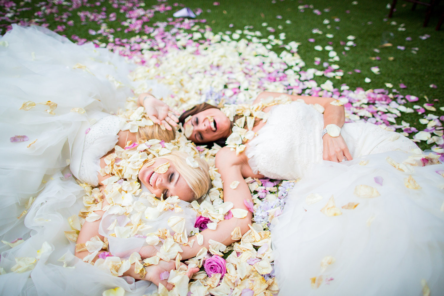 Lesbian brides laying on a bed of flower petals at their wedding