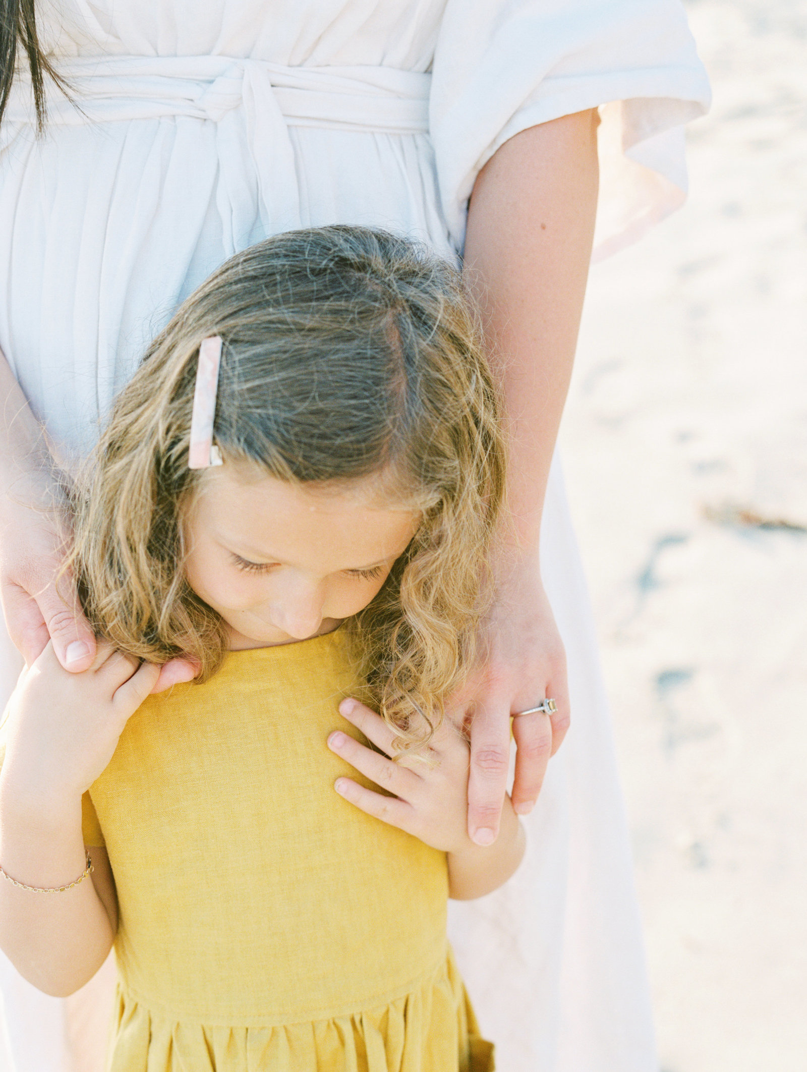 little girl in yellow dress with ringlet curls looking down and holding her mom's hands