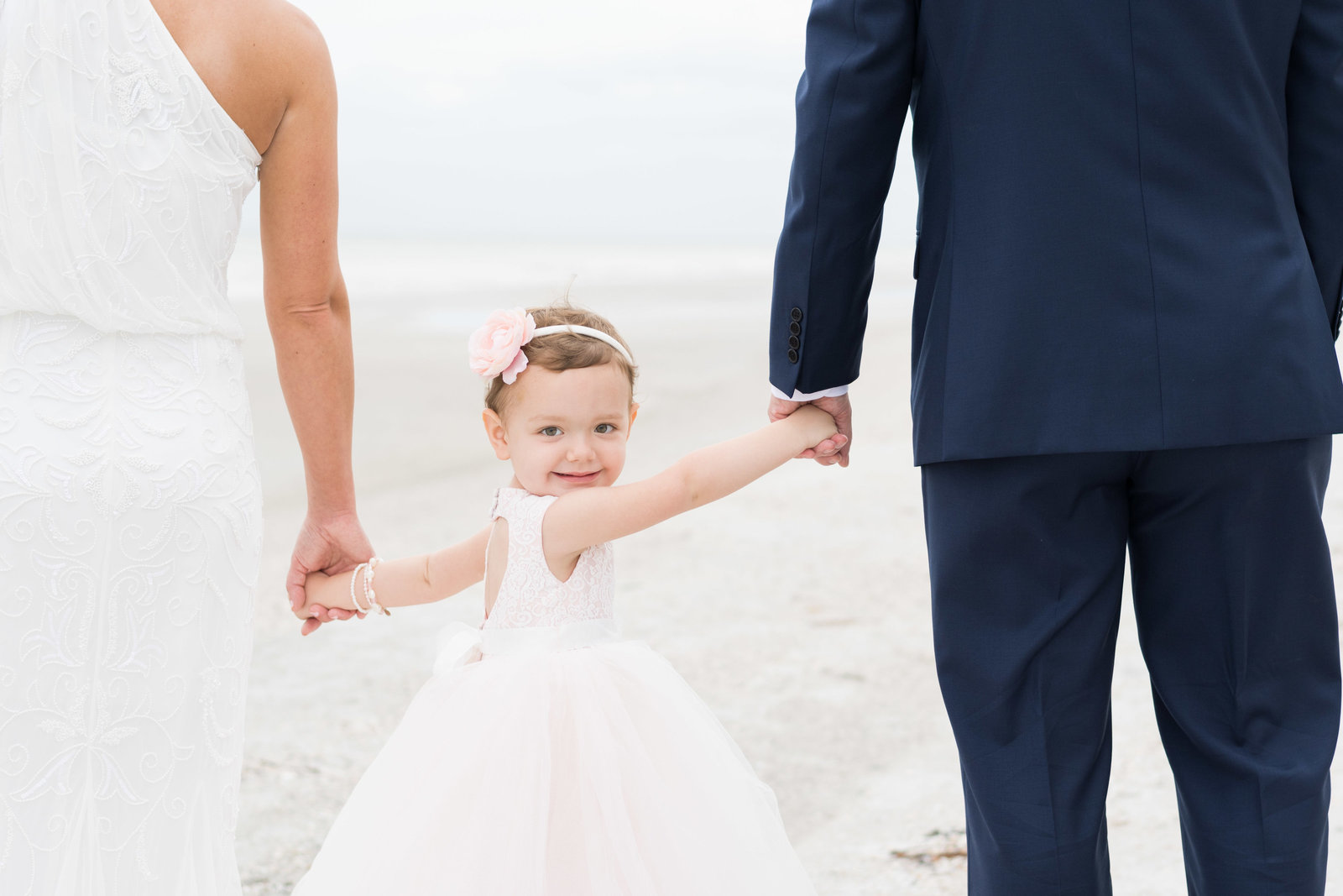 charlotte wedding photographer shot of Shot of flower girl hold bride and grooms hands