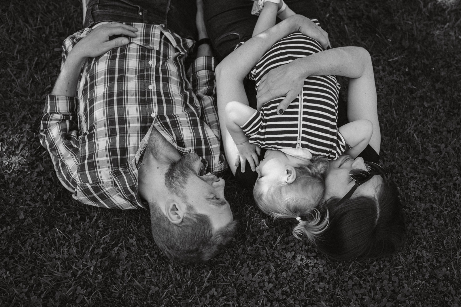 Black and white family photograph of relaxed family hugging and smiling laying on the grass in Suffolk