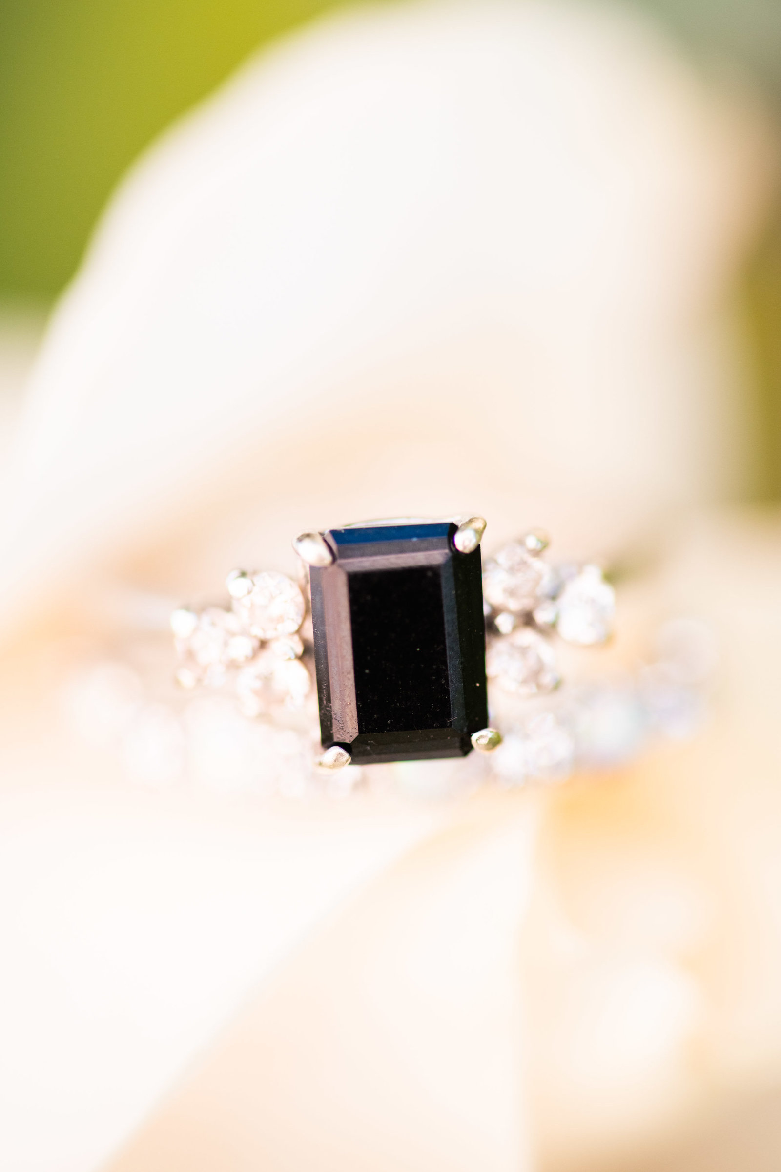 black square engagement ring on white flower