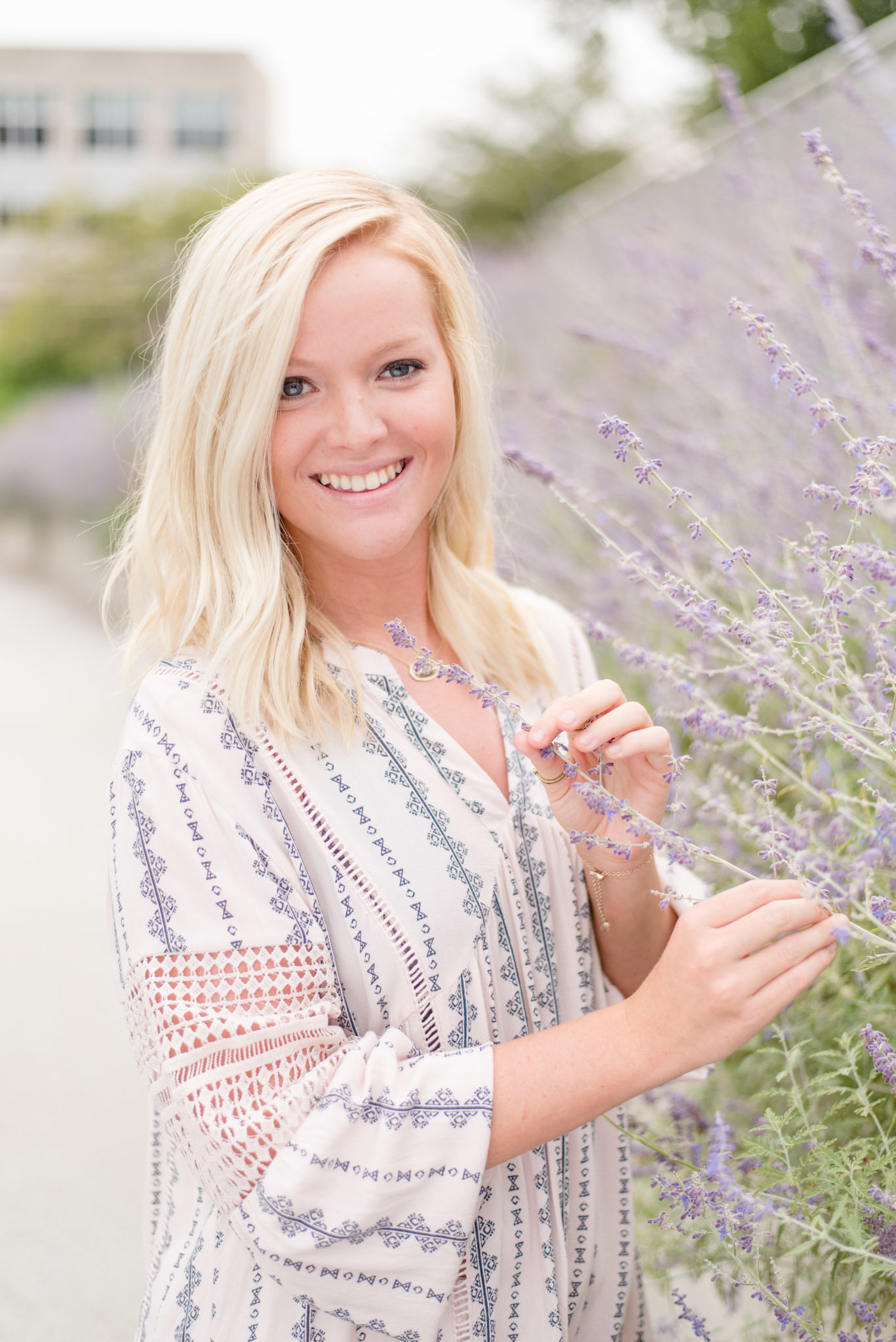 Senior holds lavender and smiles.