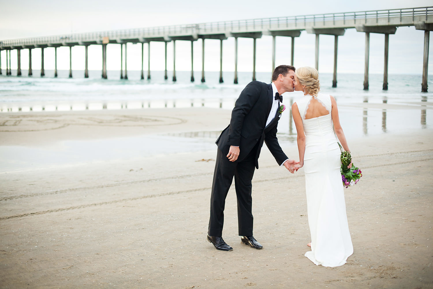 bride and groom kissing with scripps pier in the back ground