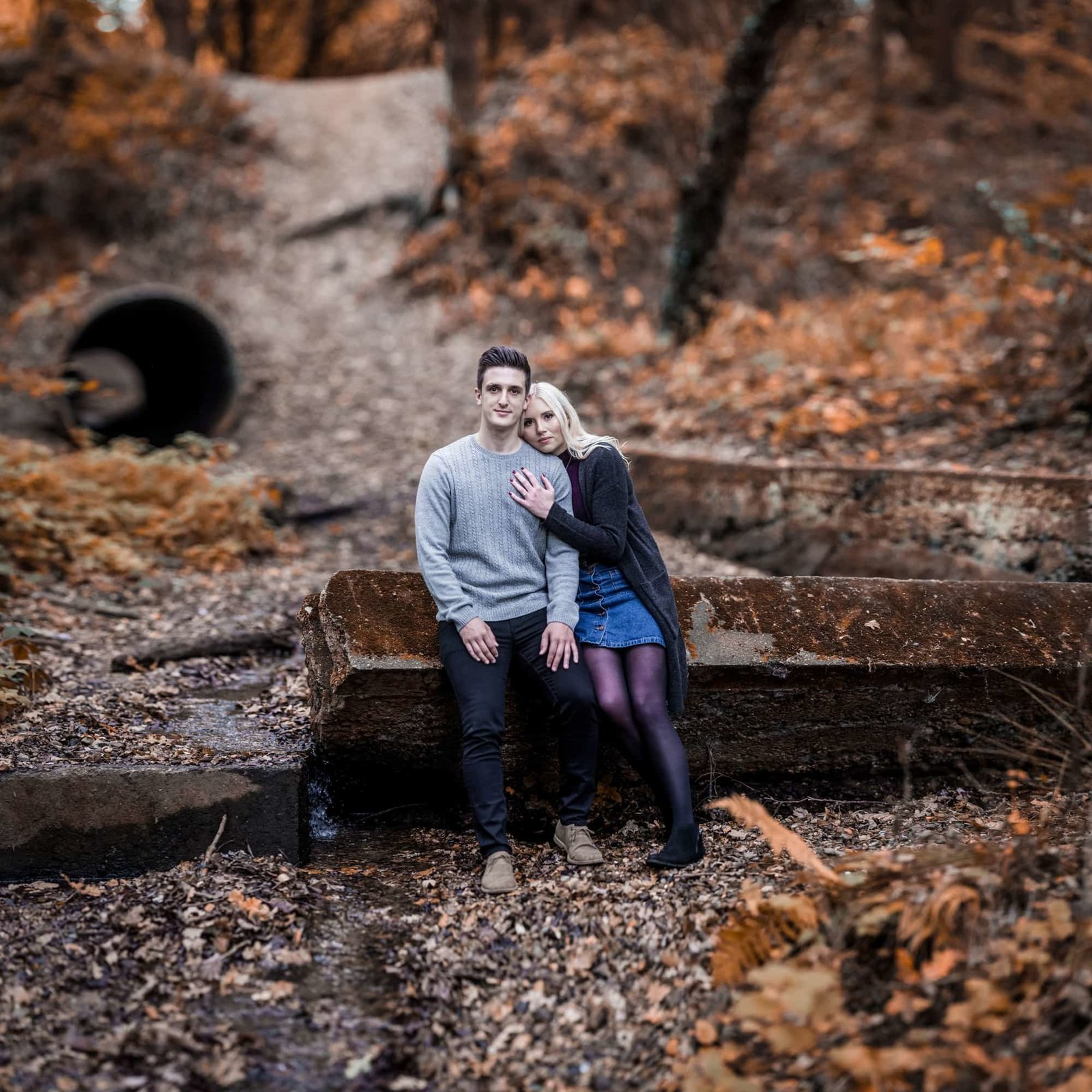 An engaged couple hug and smile at the camera whilst sat on a log in a Norfolk forest setting, it is Autumn.