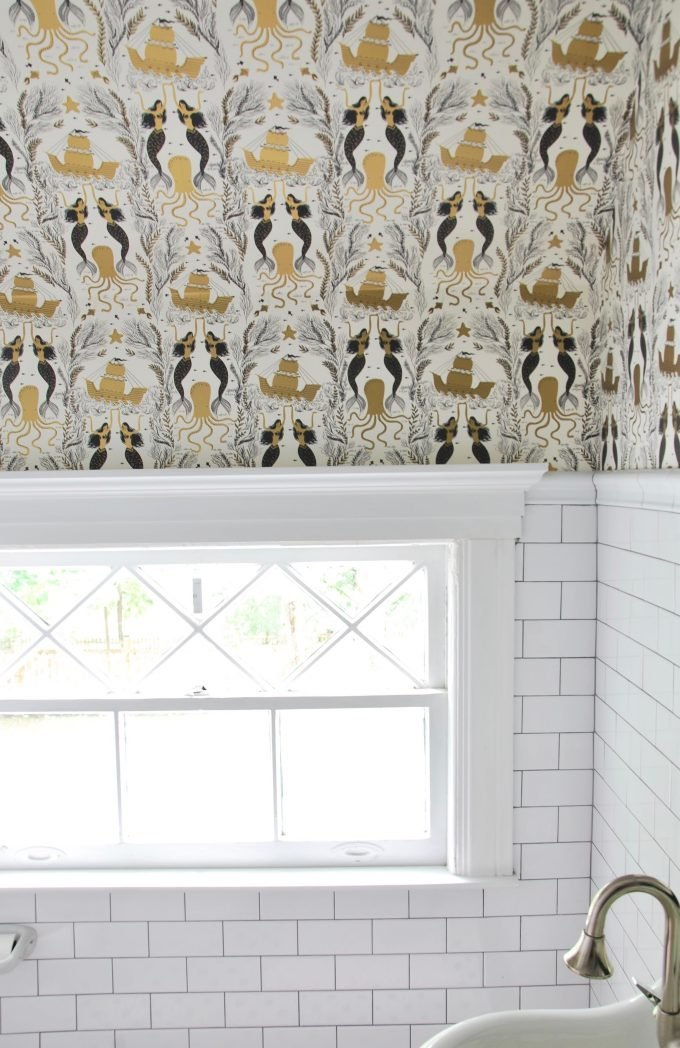 A wallpapered bathroom with subway tile and vintage sink.