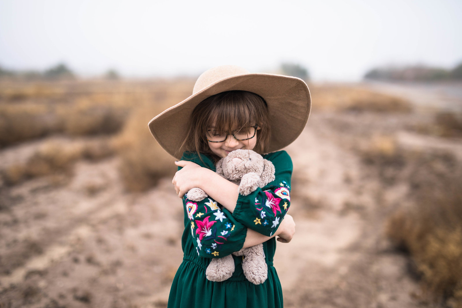 Girl in a green dress and a hat in a field hugging a stuffed bunny