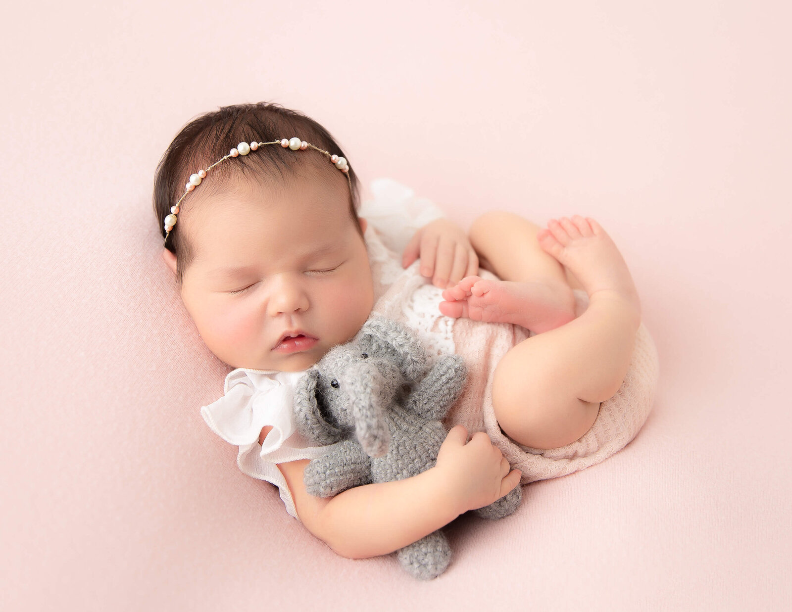 Precious newborn girl posed sleeping at our in-home Rochester, Ny studio.