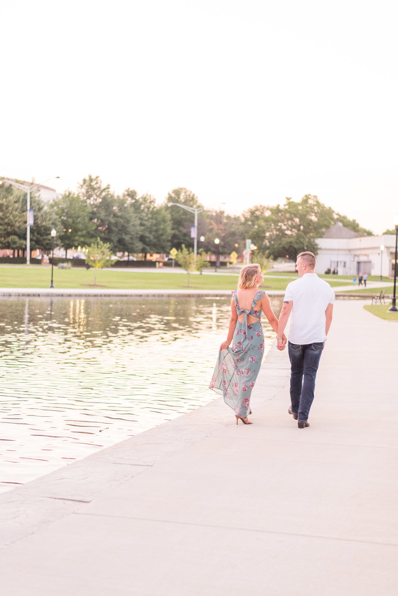 Couple walks by canal at sunset.