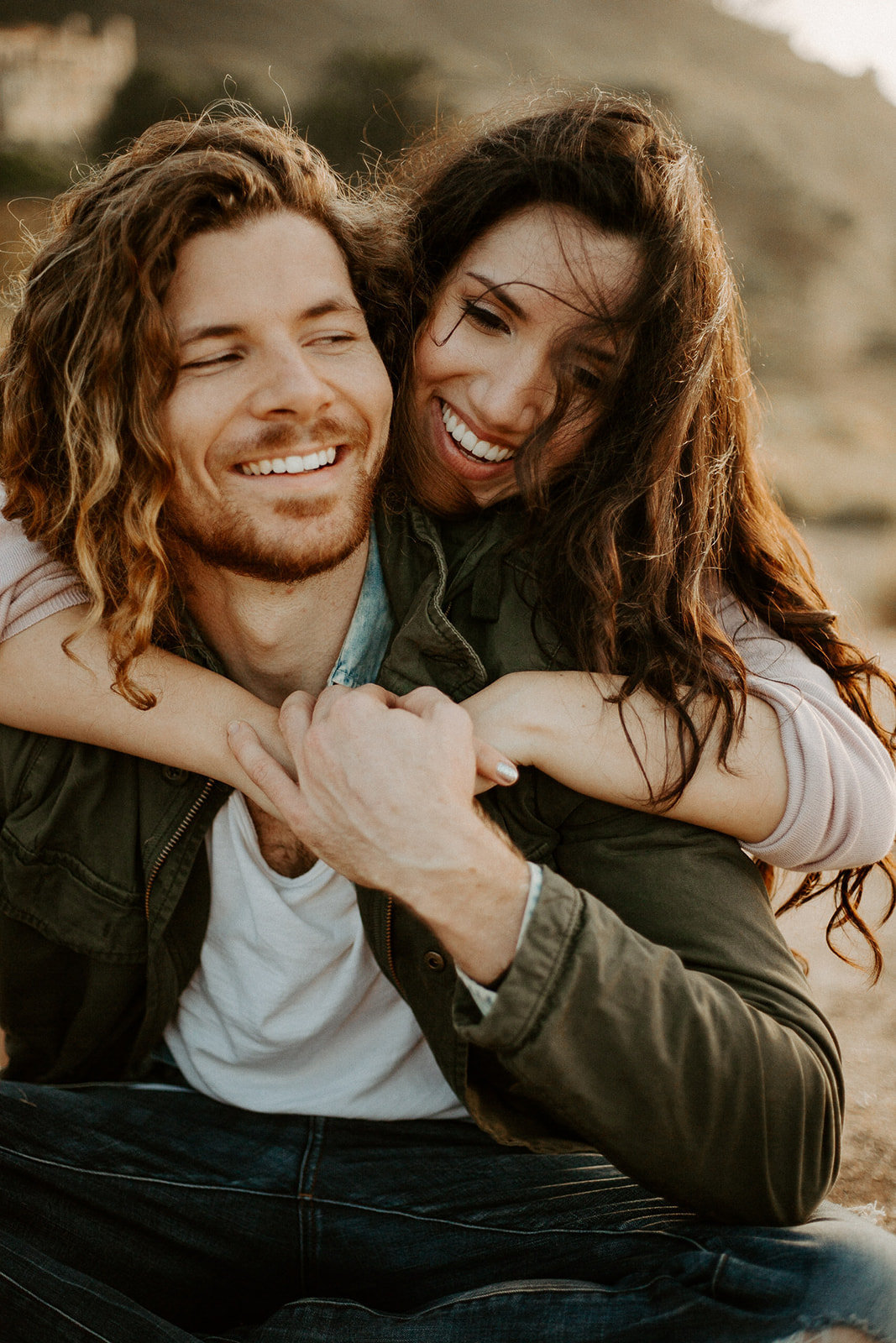 Woman hugging her man from behind during their California engagement session