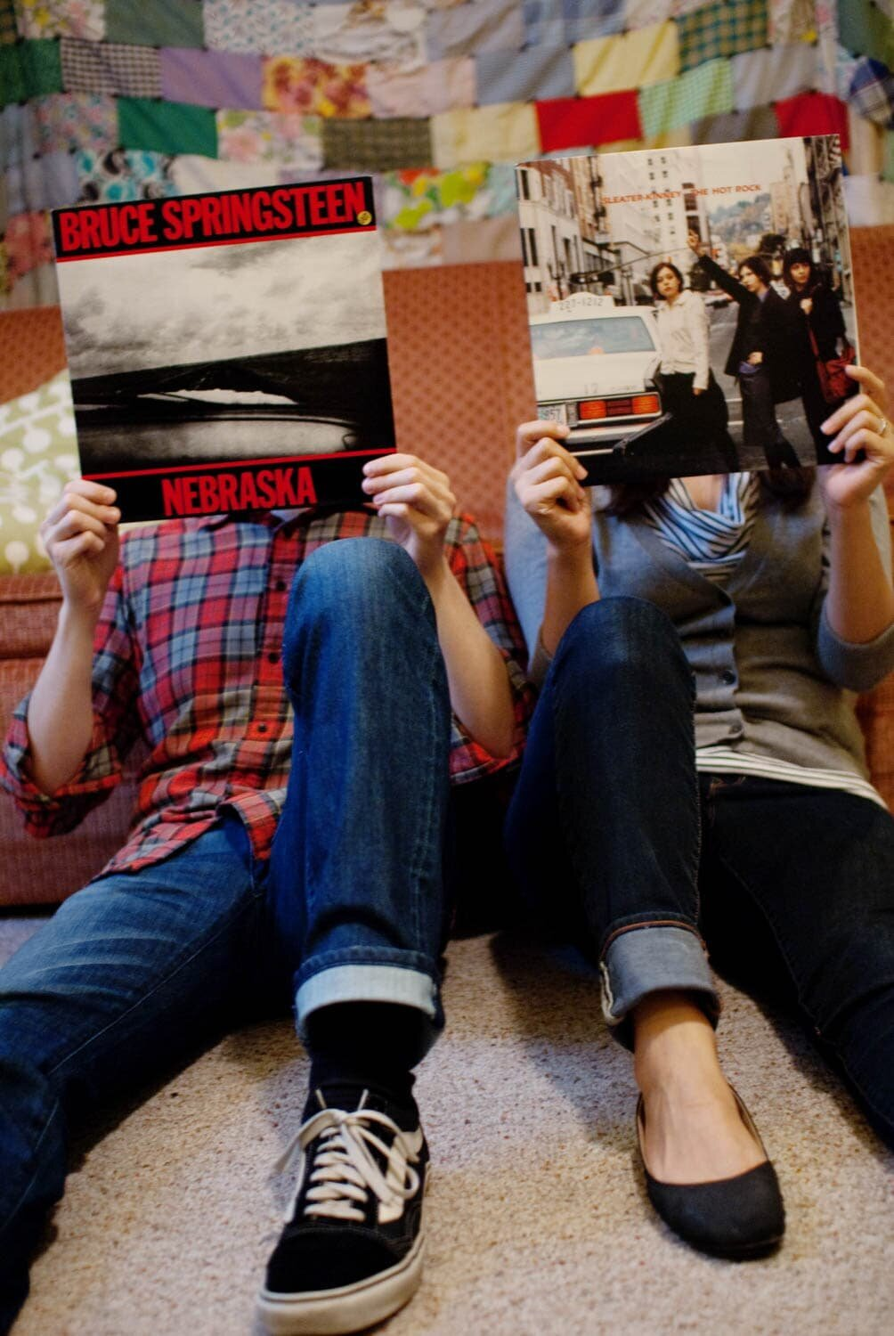 a couple cover their faces with a bruce springsteen and sleater kinney record cover