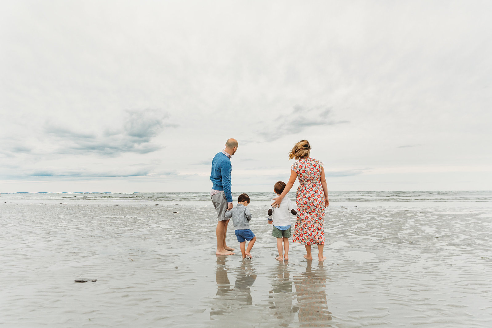 family with two boys stands and stares at ocean during family photo session in boston