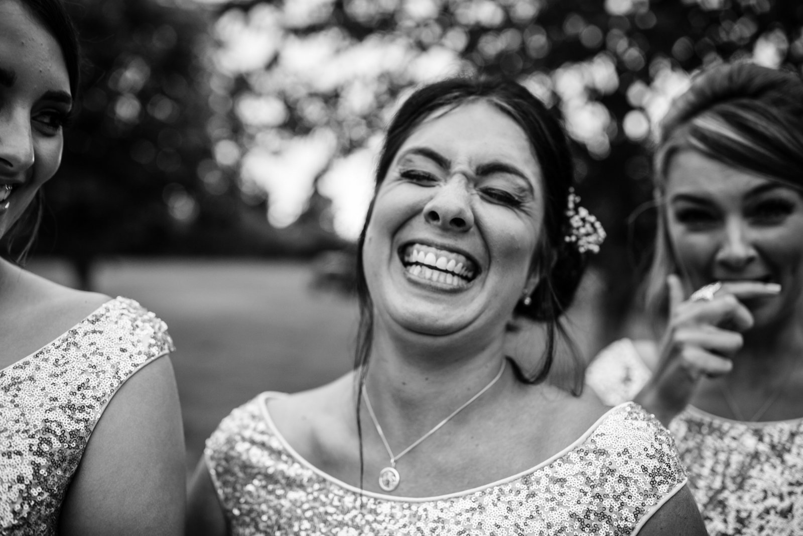 A Bridesmaid laughs uncontrollably in close up at a wedding in Norfolk. Black and white photo