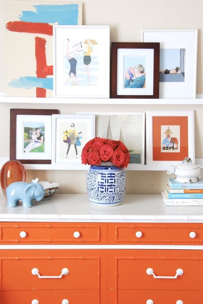 An orange white dresser with accessories and framed art and photos on shelves.
