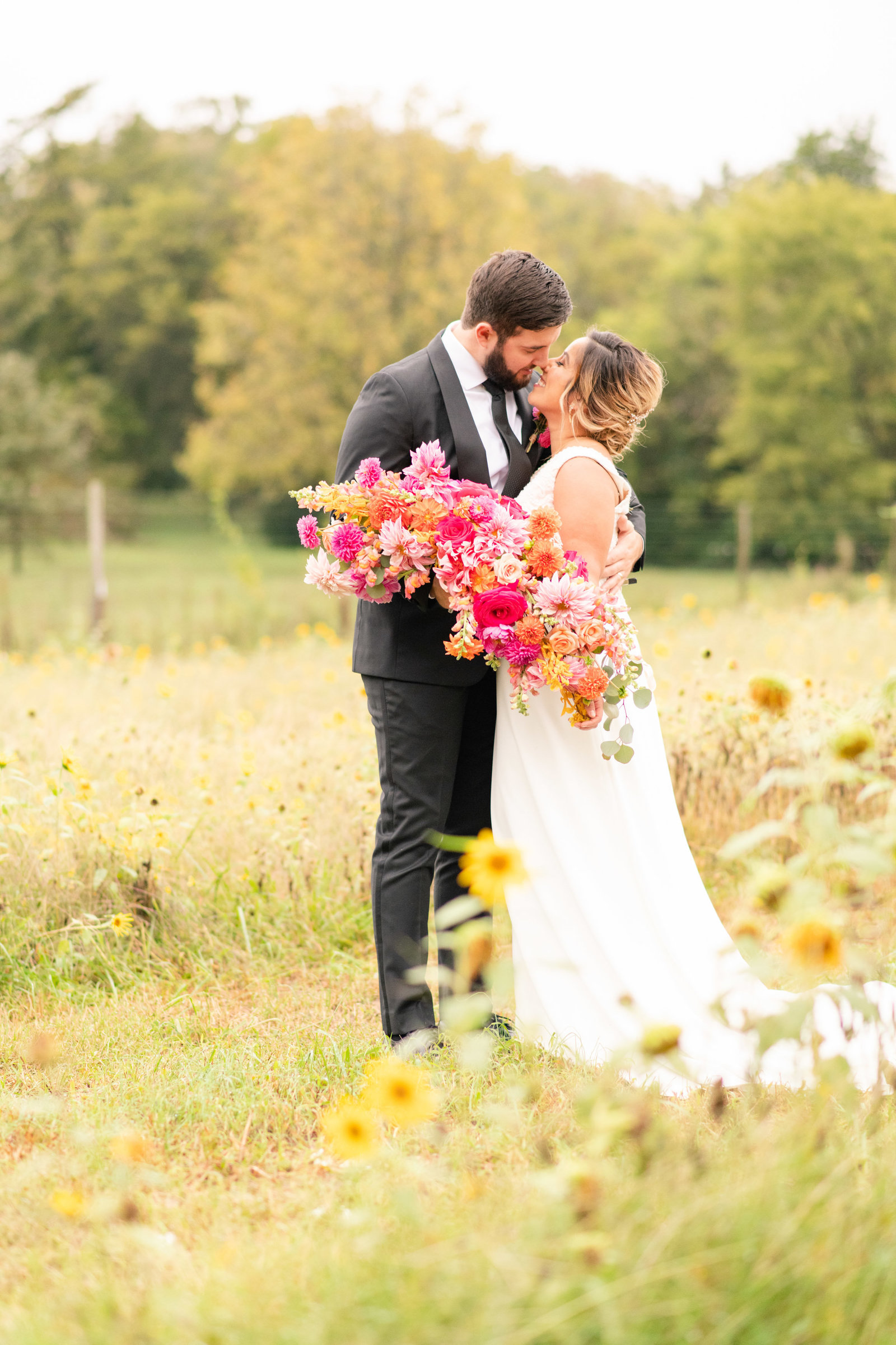 wedding couple kissing in field of wildflowers with bright pink bouquet