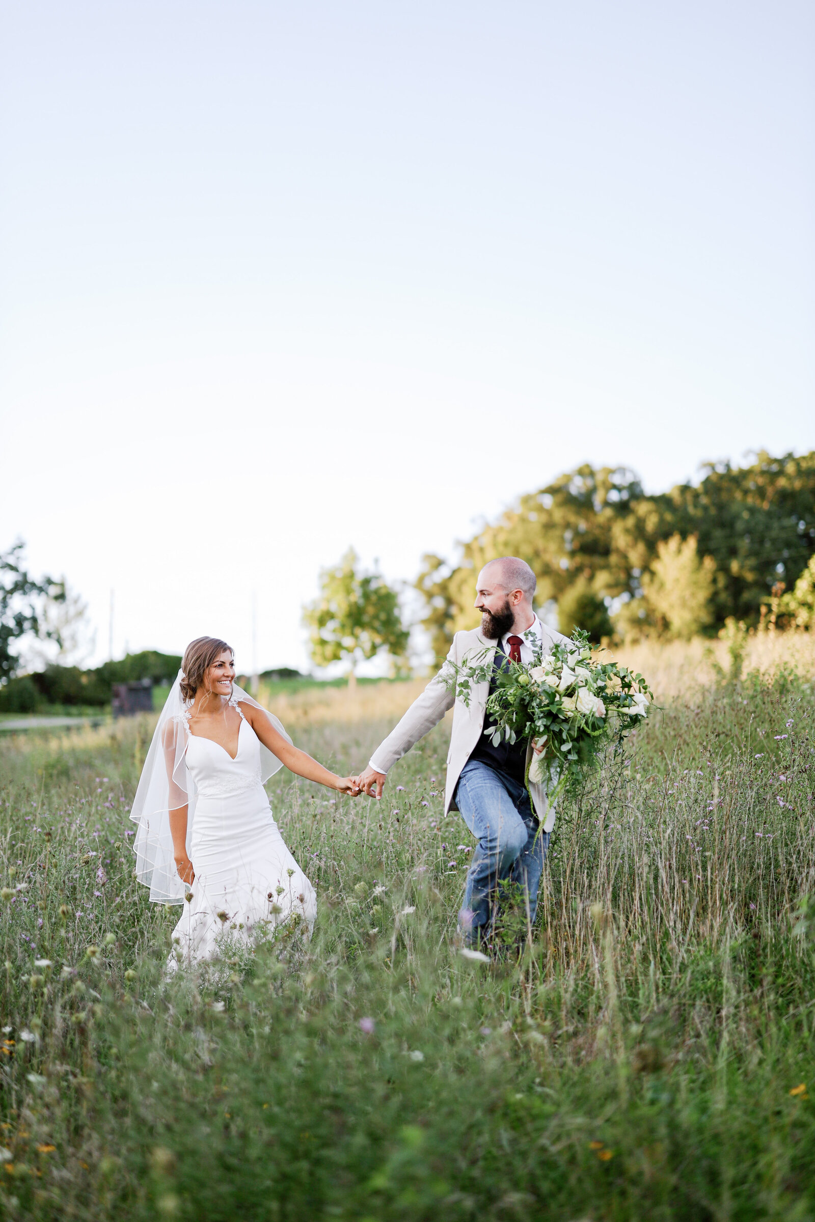 Modern wedding couple with classic florals walking through a field