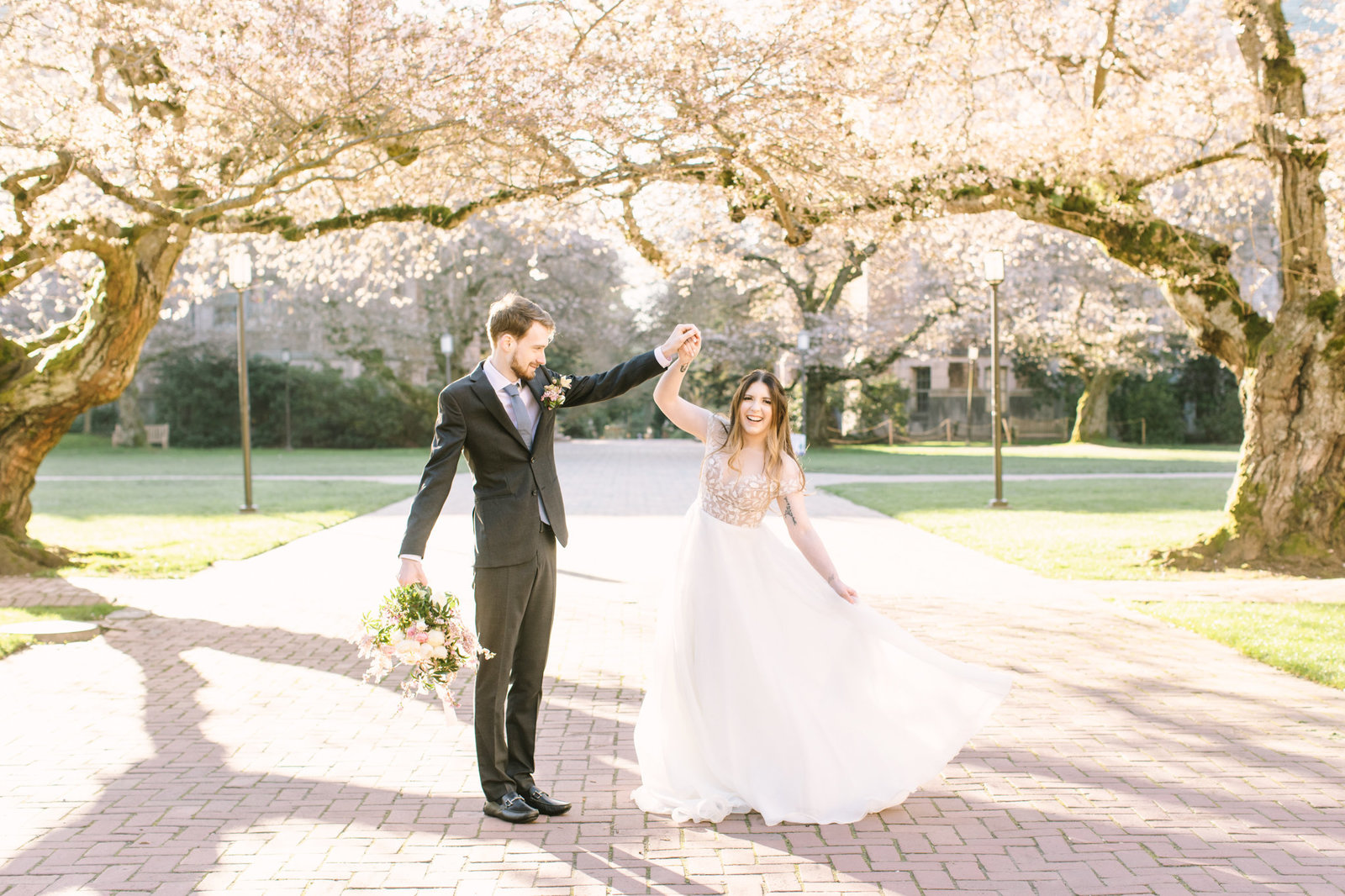 bride and groom dancing with the UW Quad cherry blossoms