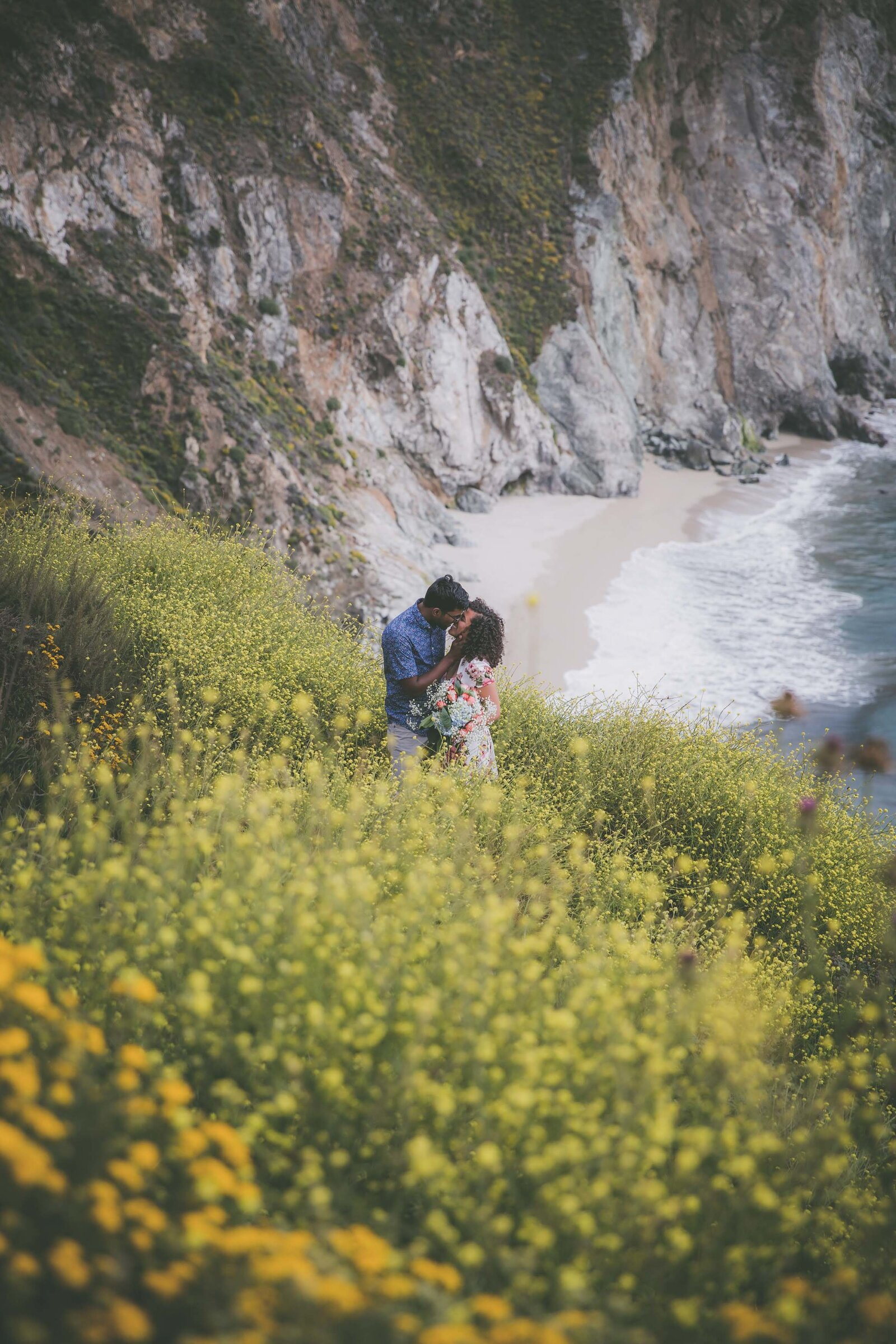 Couple kisses in field on yellow wildflowers by ocean in Big Sur.