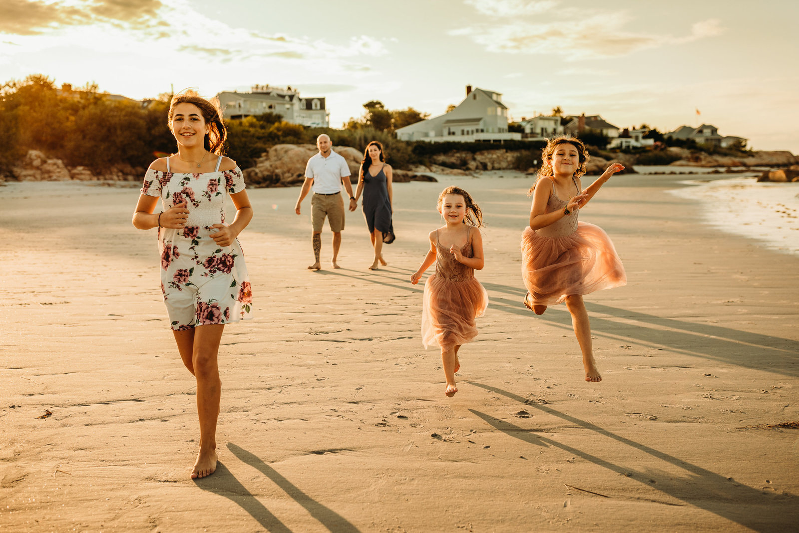 three sisters run towards camera on beach during family session on north shore boston