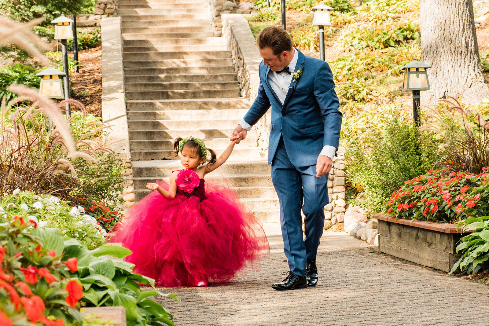 Groom walking flower girl down isle