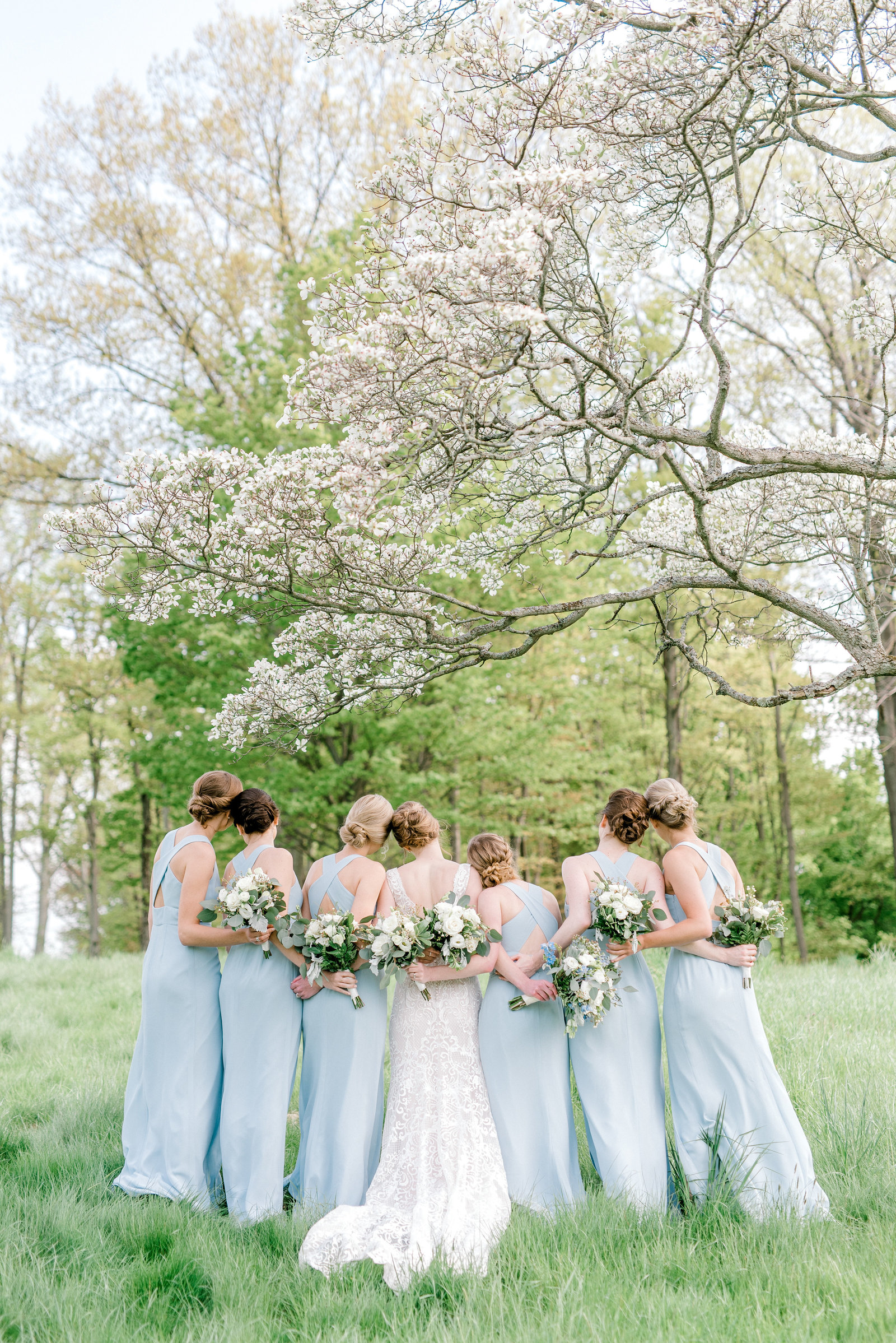 Spring Wedding in Erie PA with gorgeous blue dresses and flowering trees
