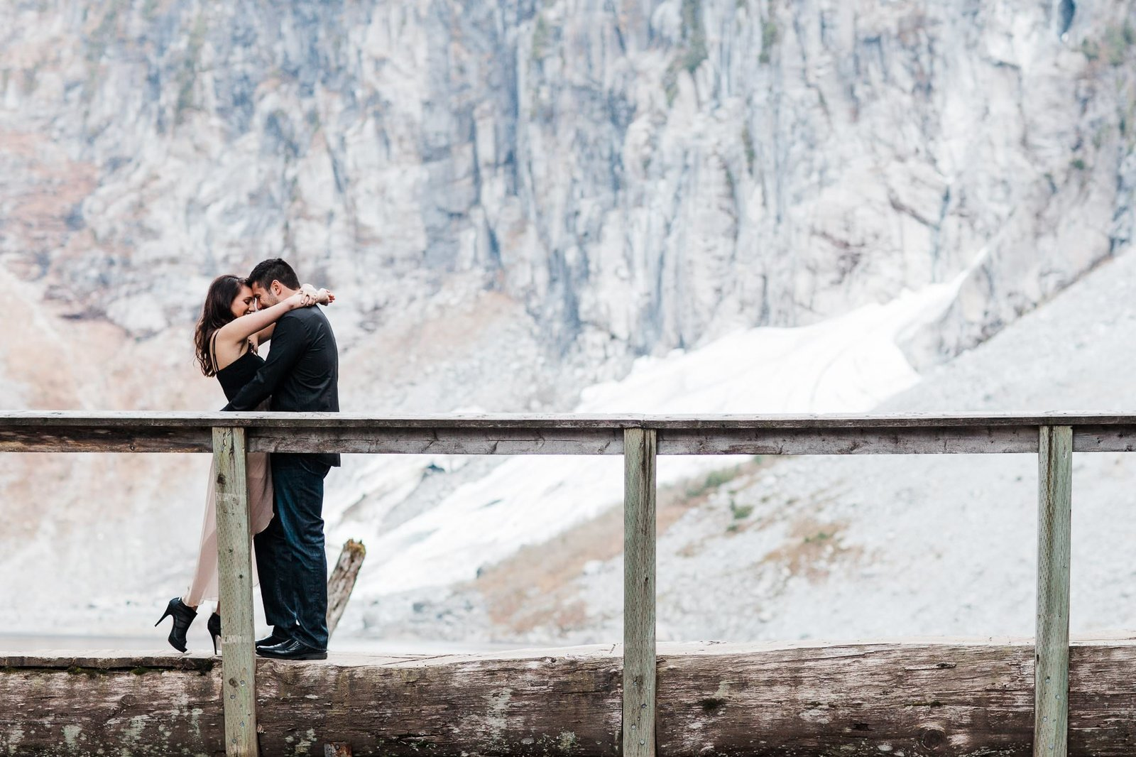 Amy Galbraith's image of a couple snuggling close together on a bridge during an adventure engagement session at Stevens Pass