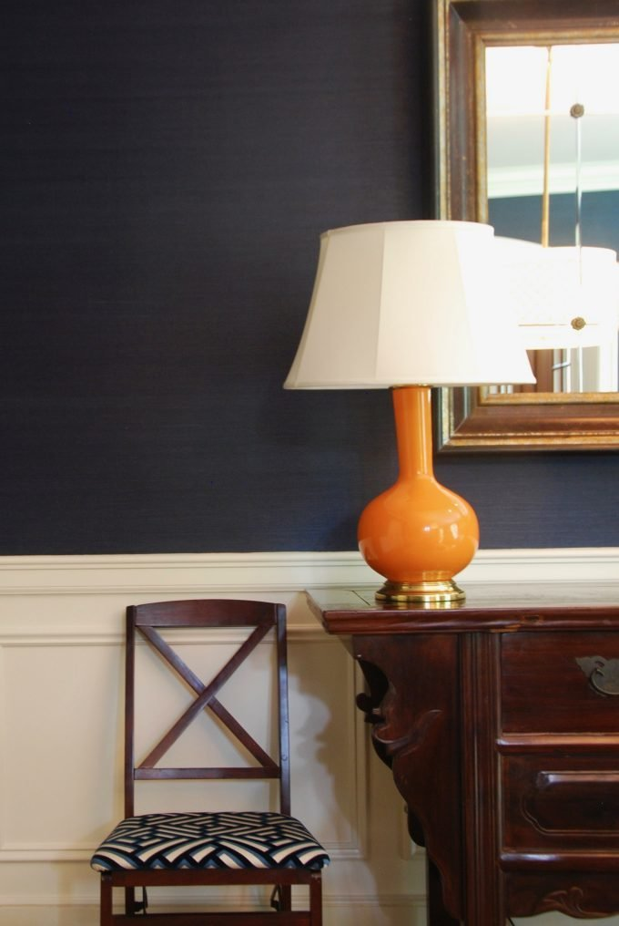 An orange lamp on a wooden sideboard next to a chair.