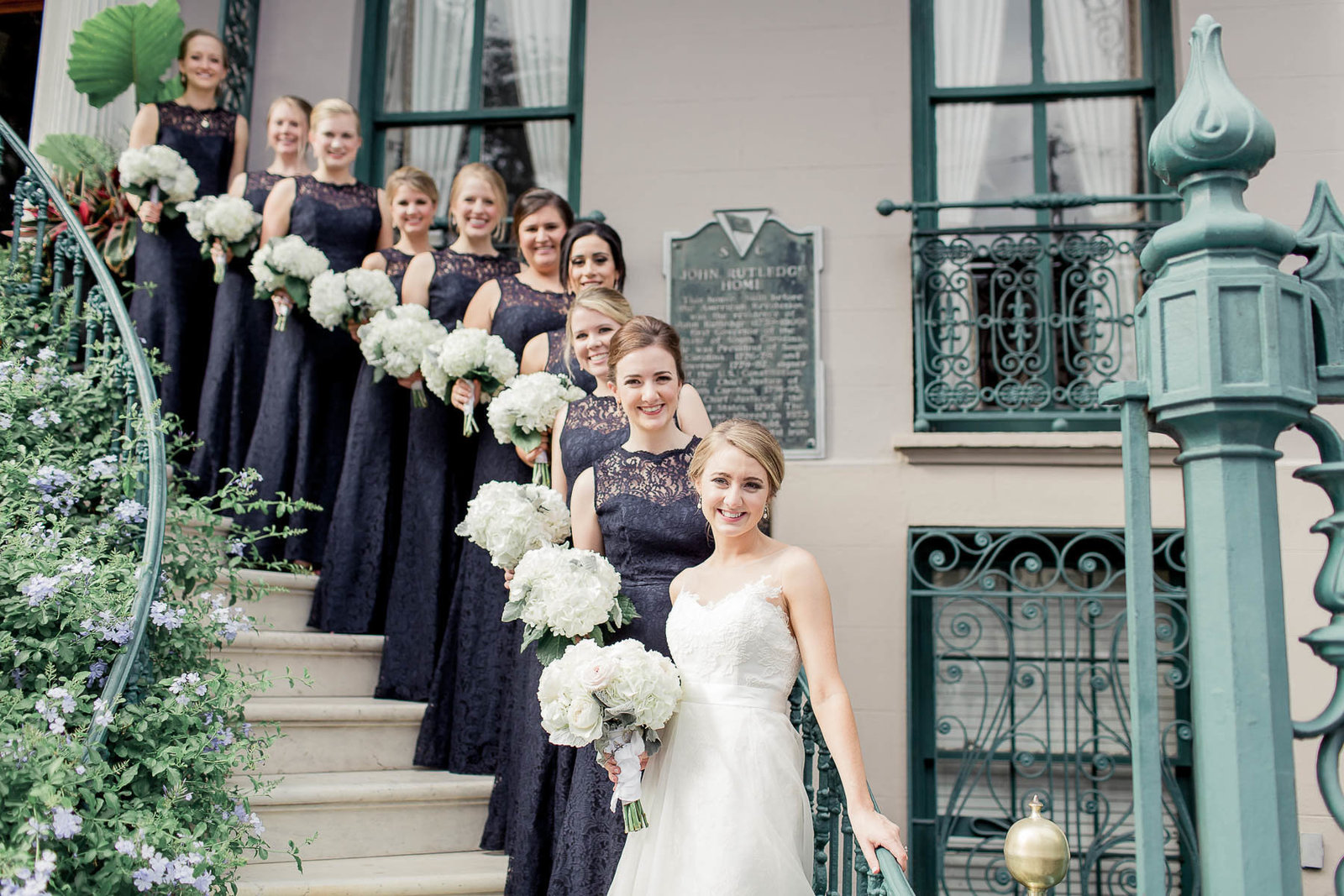 Bride poses with bridesmaids on ornate staircase, John Rutledge House Inn, Charleston, South Carolina