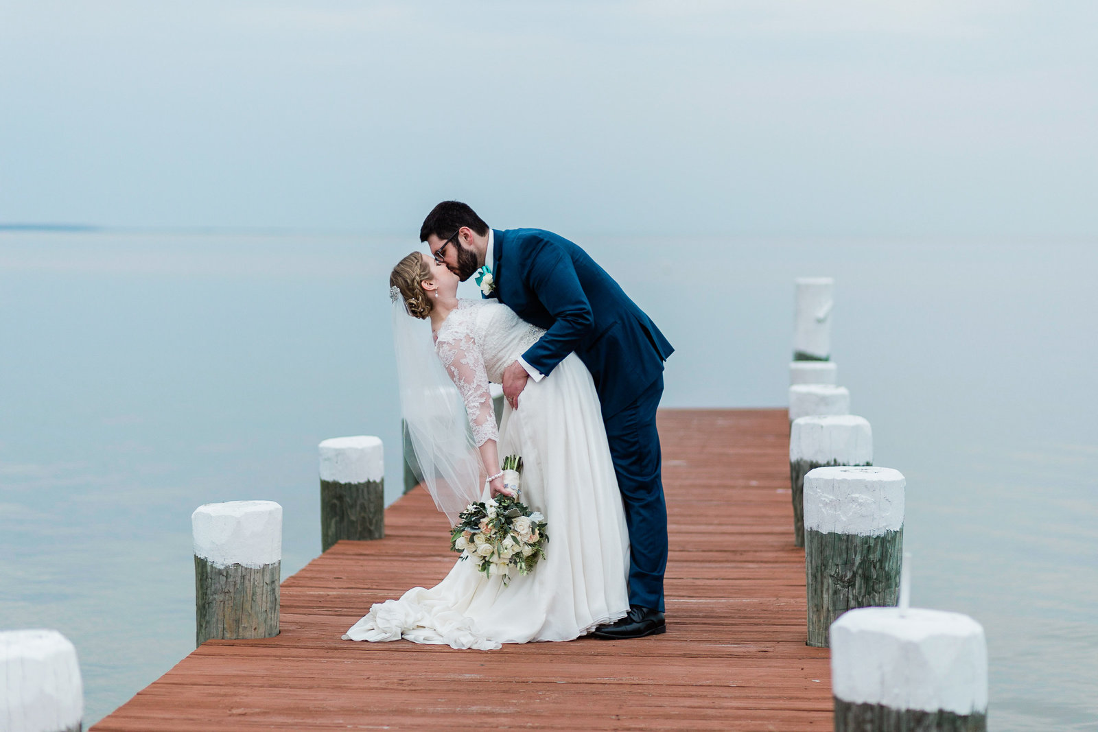 Groom dips bride for a kiss on a dock, overlooking the ocean. Celebrations at the Bay MD
