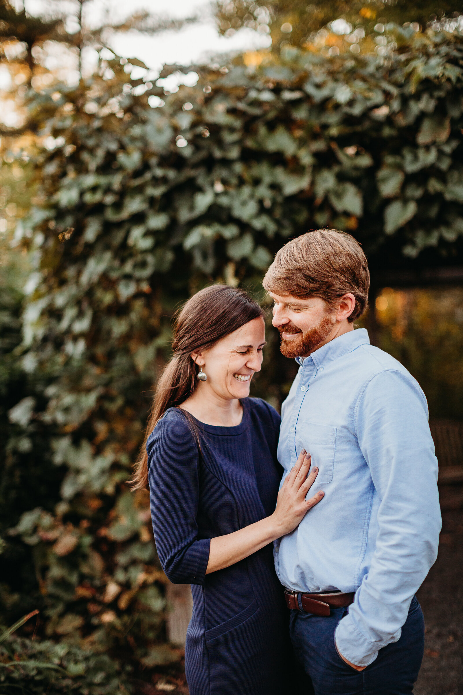 couple laughs together in front of ivy in massachusetts