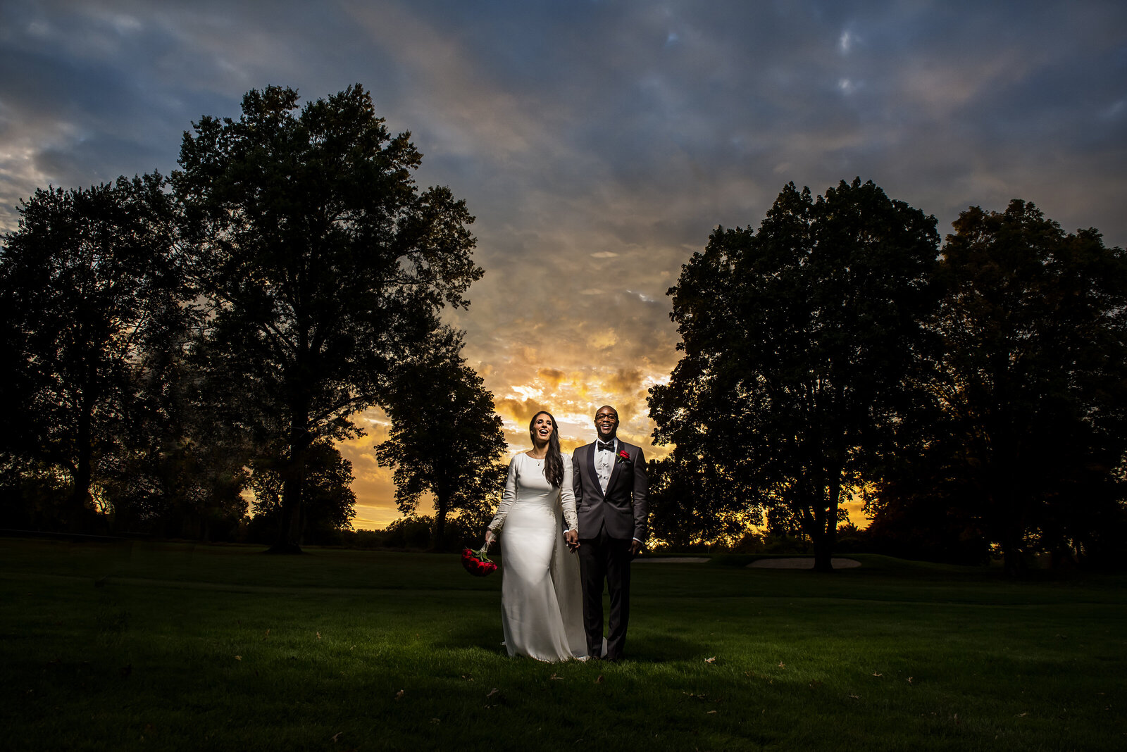 A white bride and black groom  stand happily on a gold course, with extreme colors in the sky.