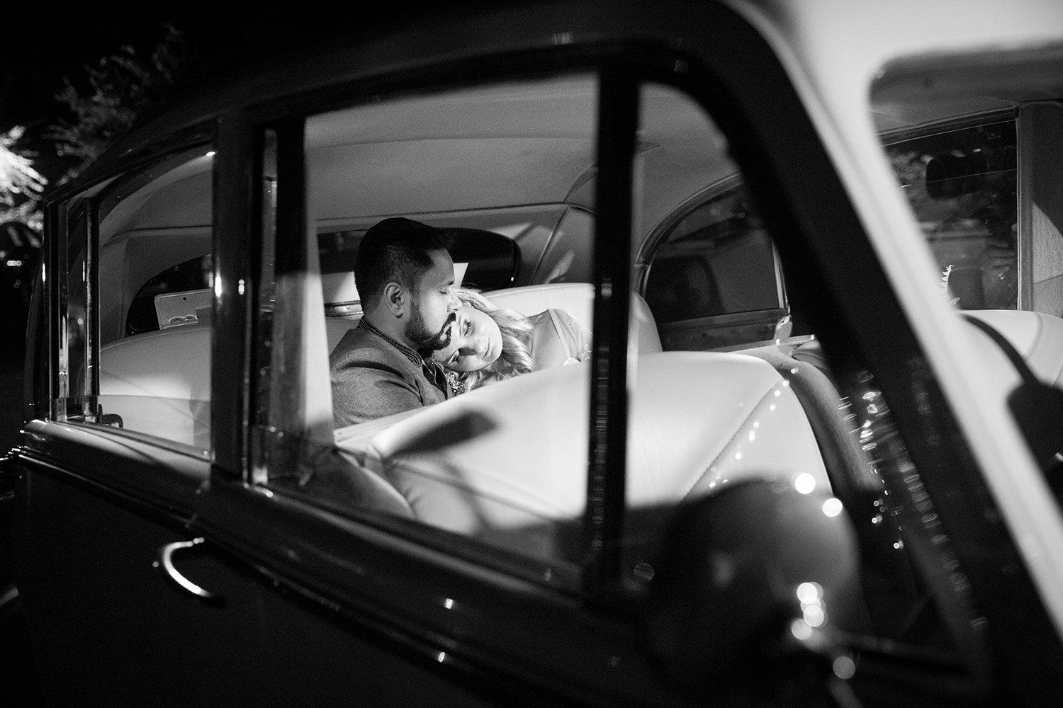 Creative portrait of bride and groom snuggling in the back of a vintage car