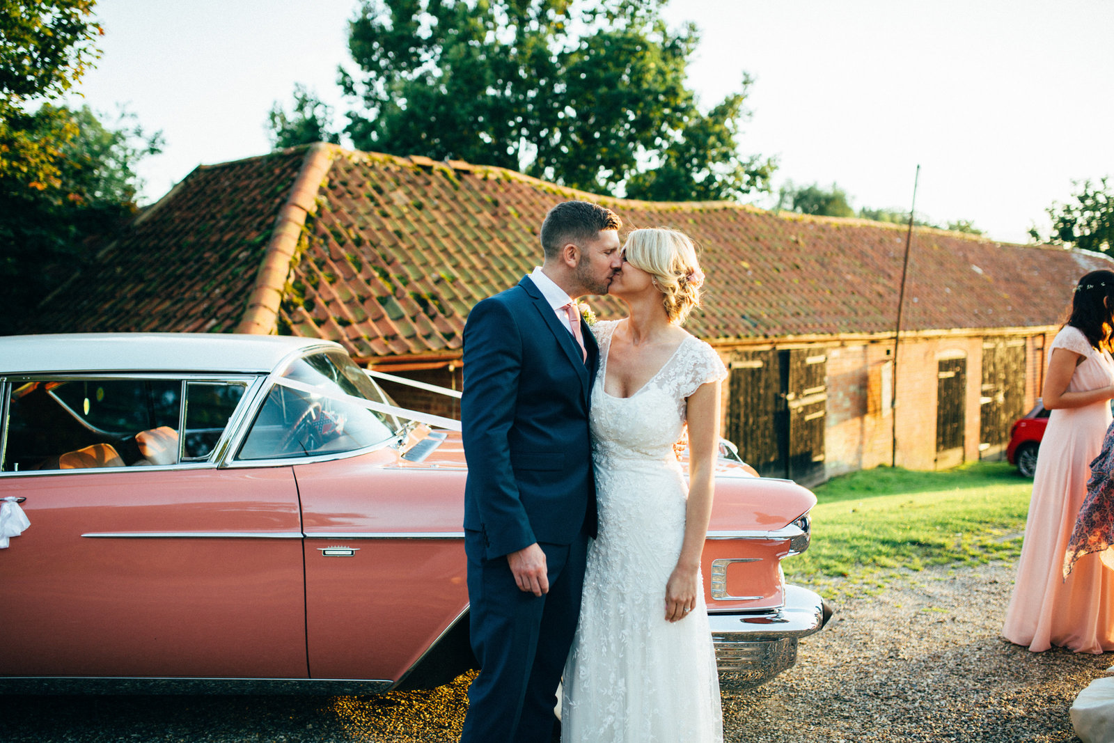 Bride and Groom kissing at sunset in front of coral vintage car at St Georges Theatre, Great Yarmouth in Norfolk wedding