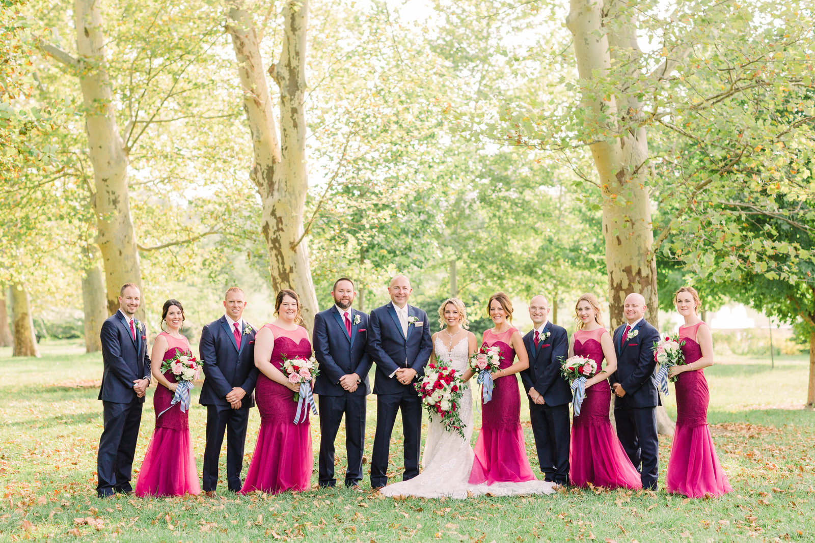 This wedding party stands in a open area of bright green on a summer day, the bridesmaid's burgundy dresses pop with color