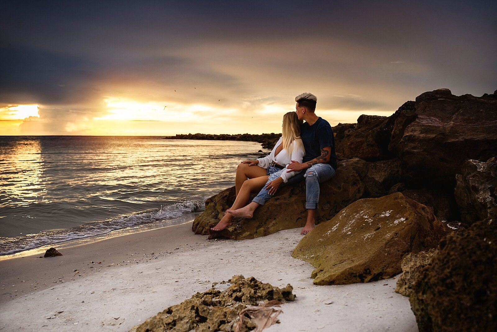 couple sitting on rocks watch clearwater beach sunset