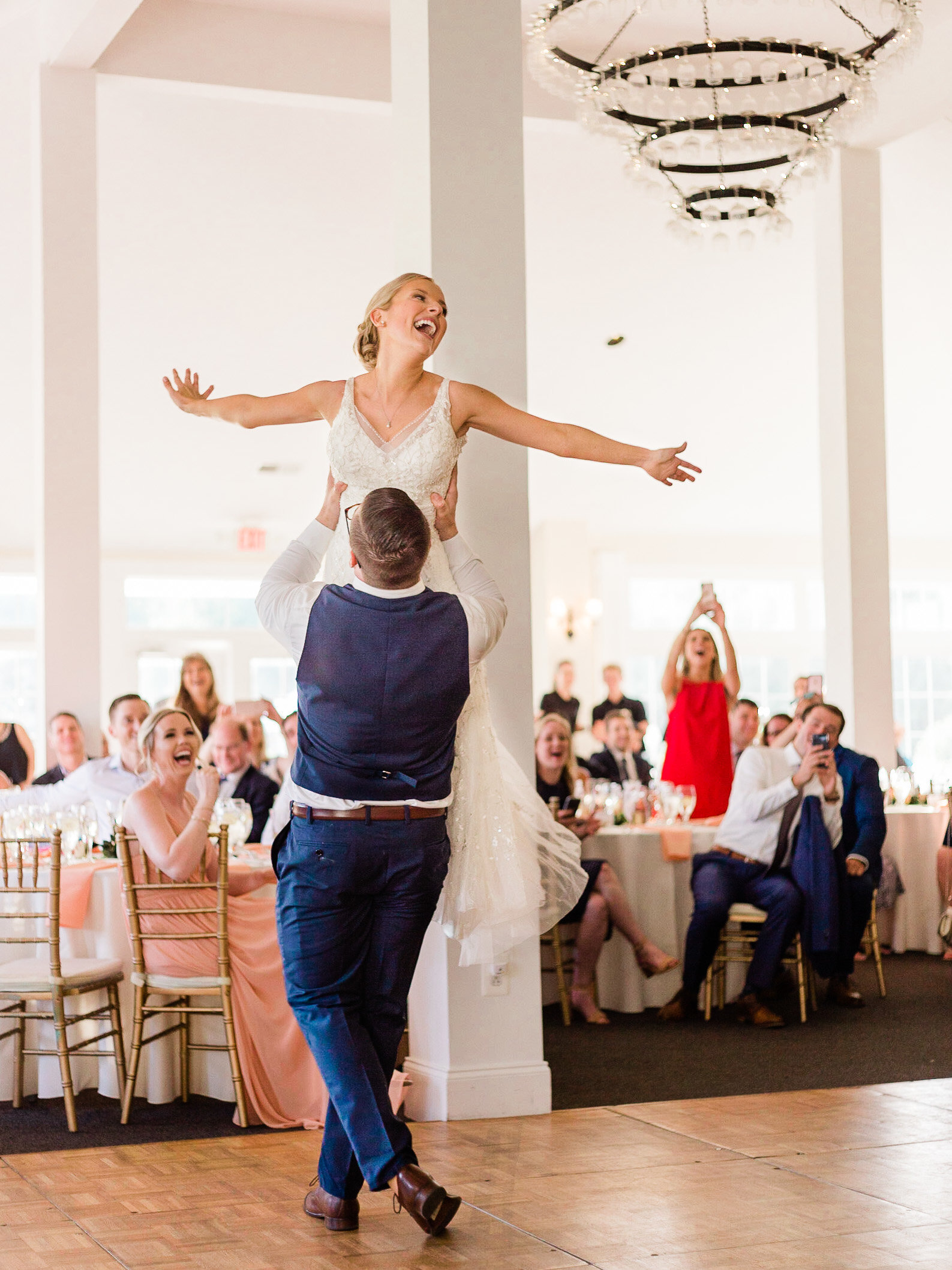 Groom lifts bride into the air during their first dance
