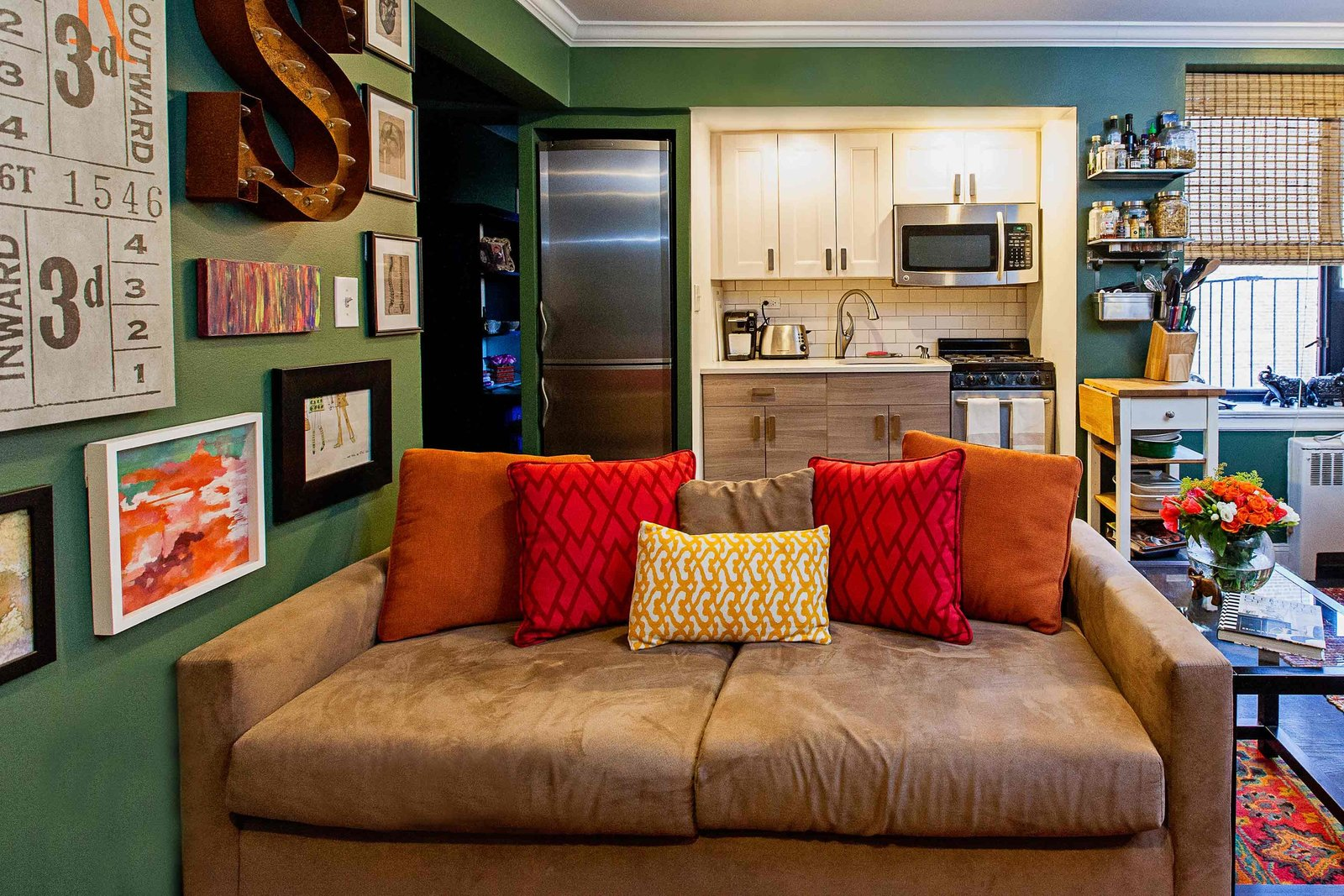 A brown couch in front of a studio apartment kitchen.