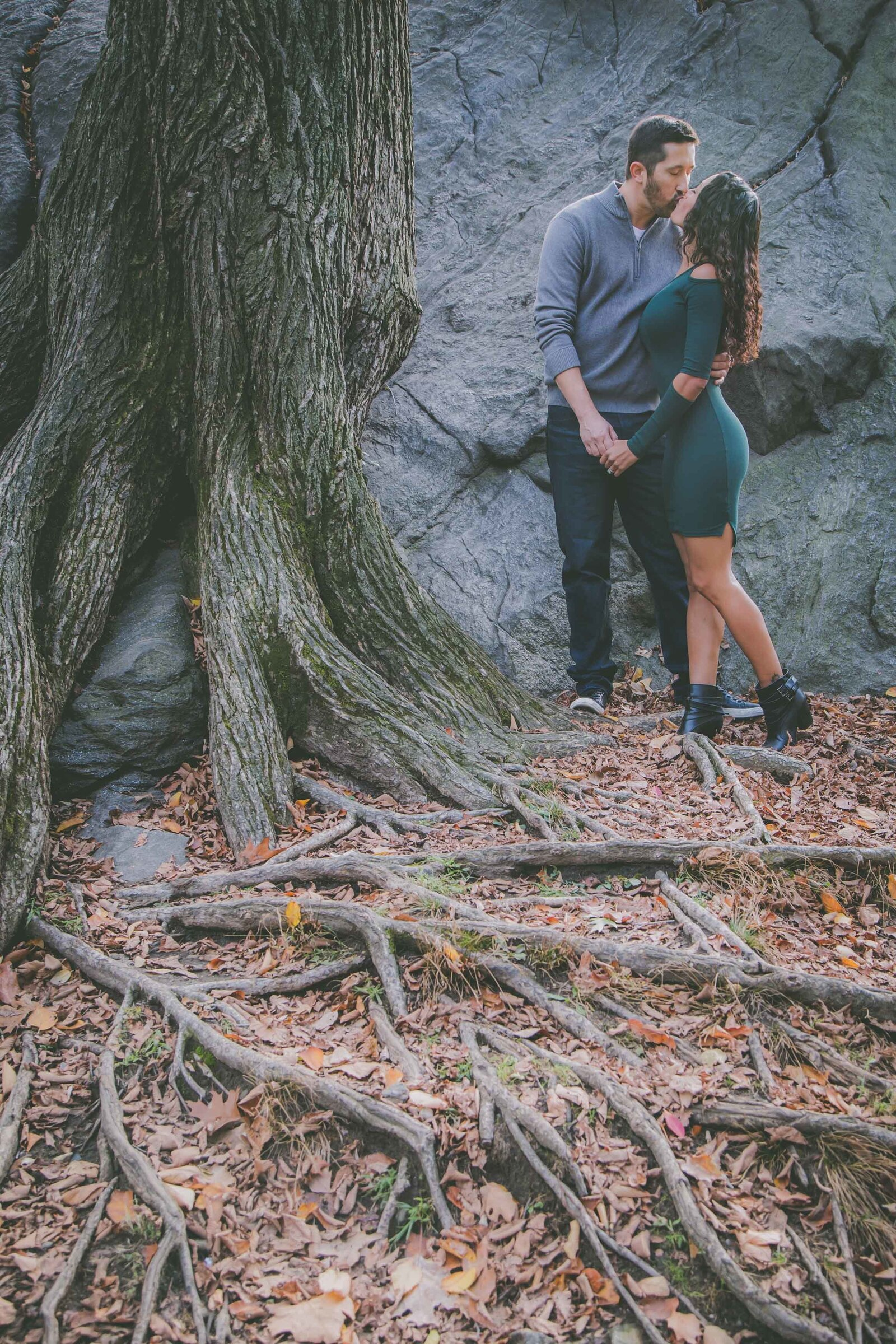 A couple kisses and hold hands by tree roots in Central Park.