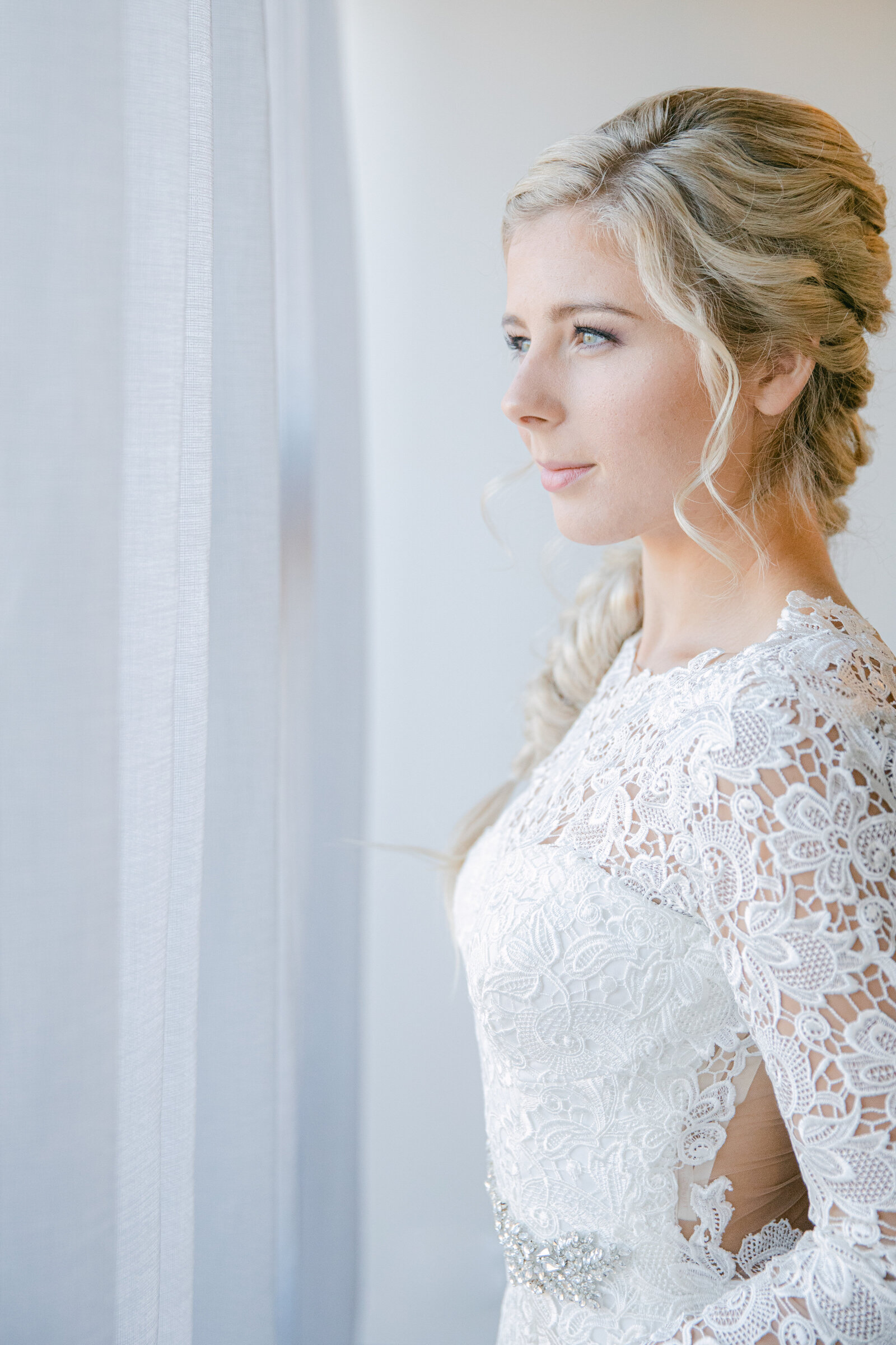 bride in lace dress looking out the window
