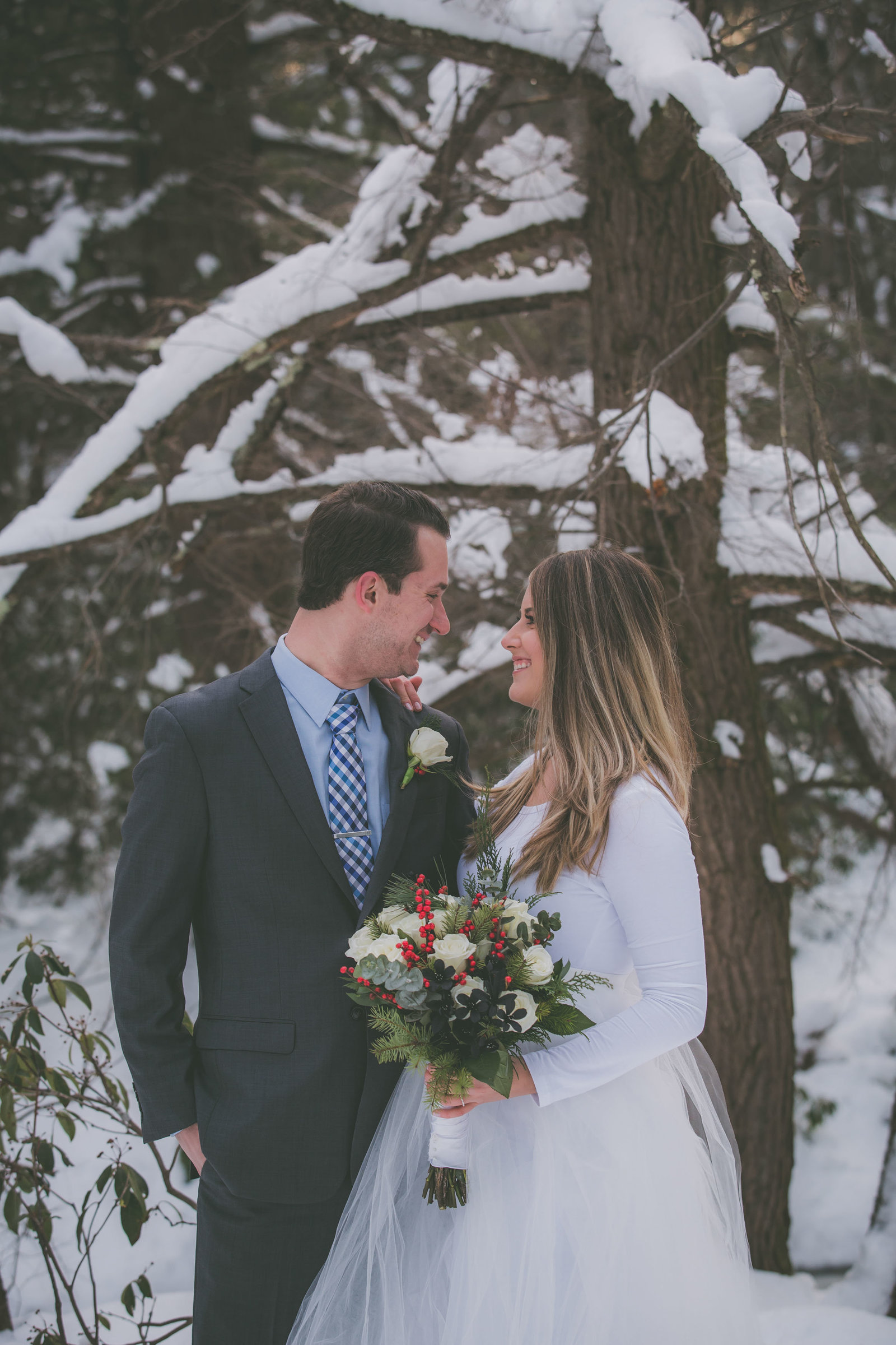 Groom and bride look at each other in woods covered by snow.