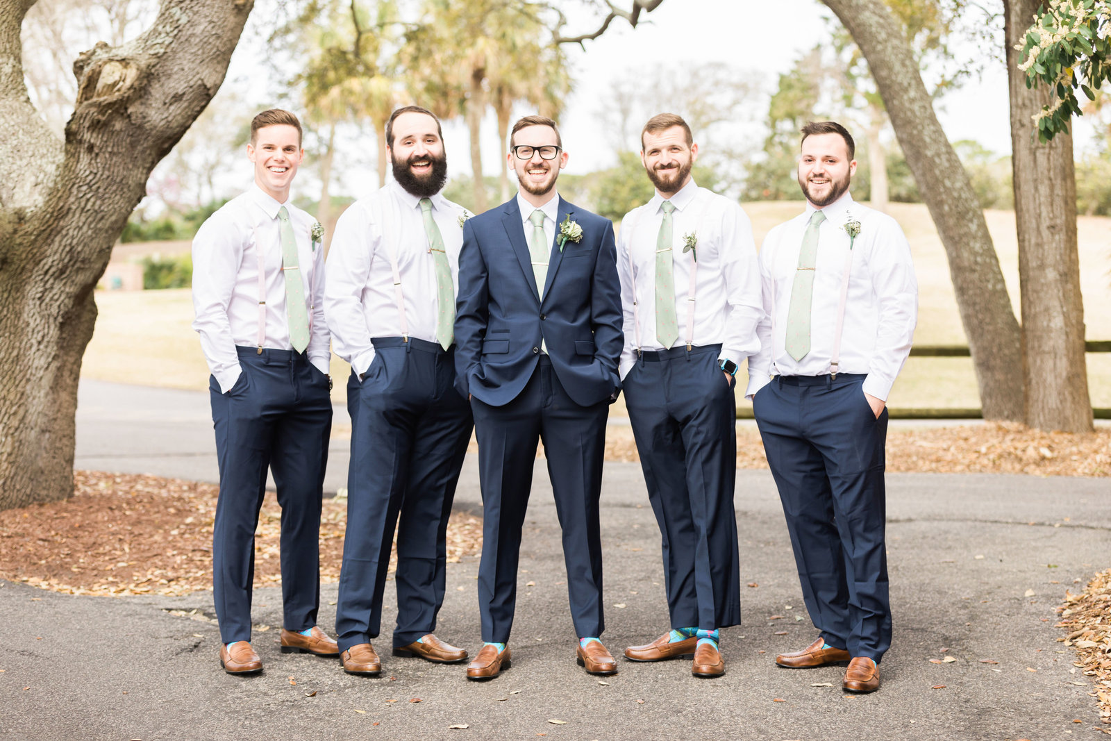 groom posing with groomsmen under live oaks