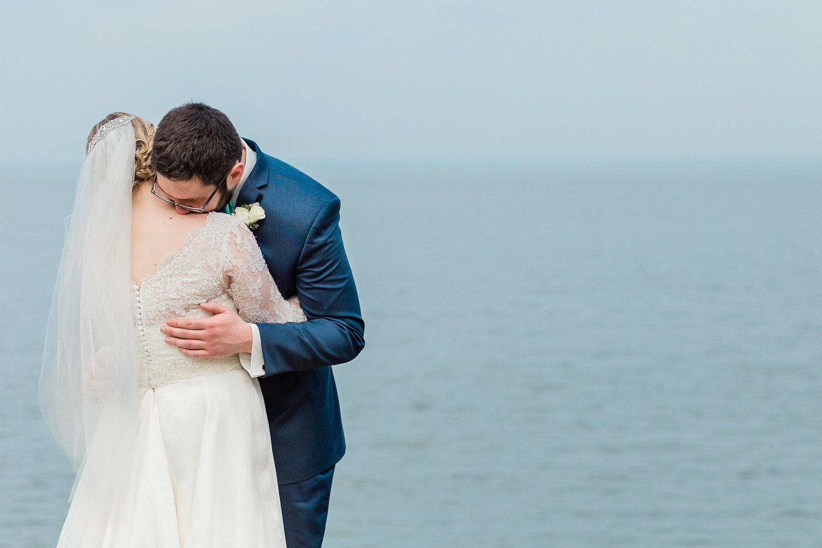 Bride and groom hug tenderly, with ocean behind them. Celebrations at the Bay Maryland