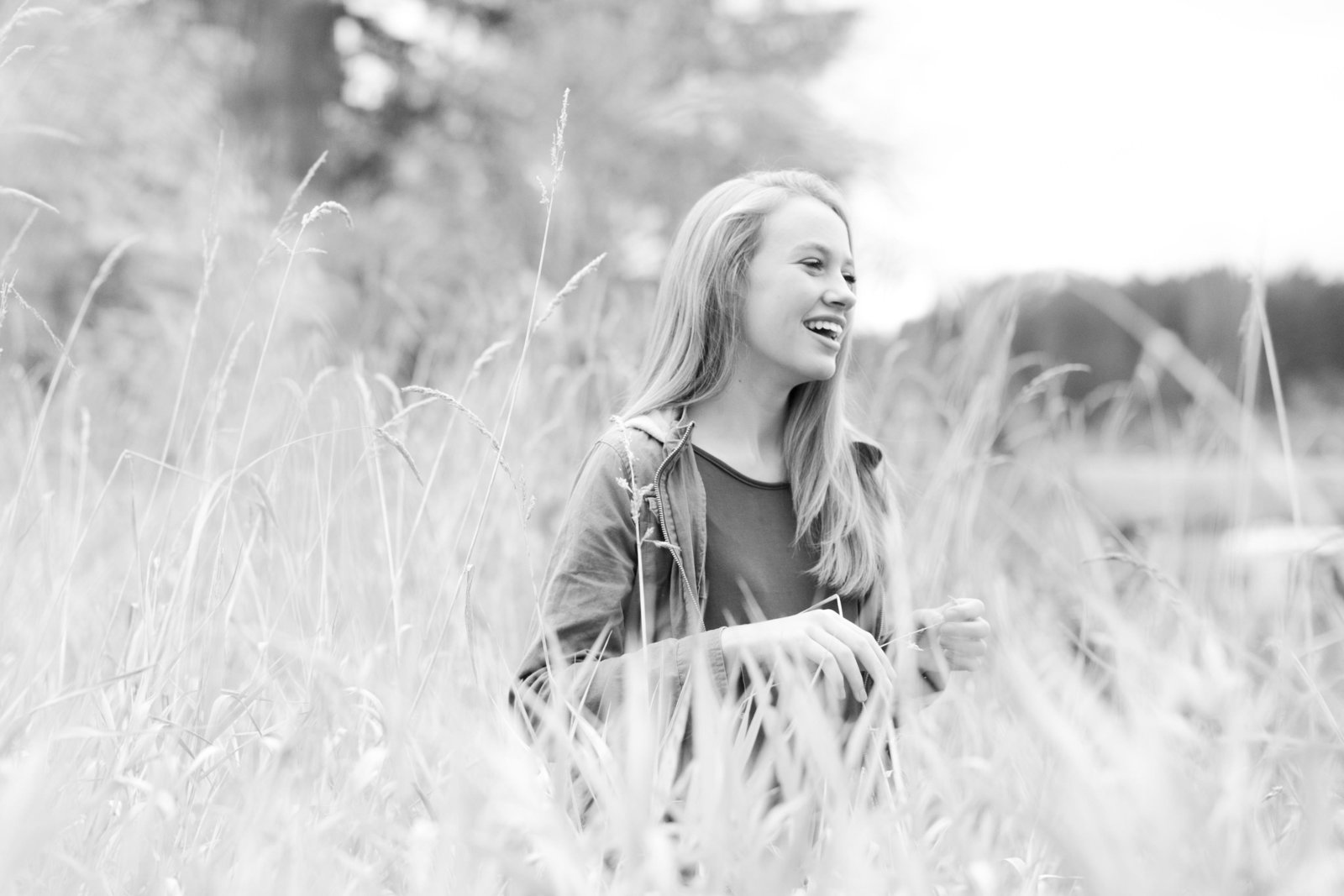Girl laughing in tall grass