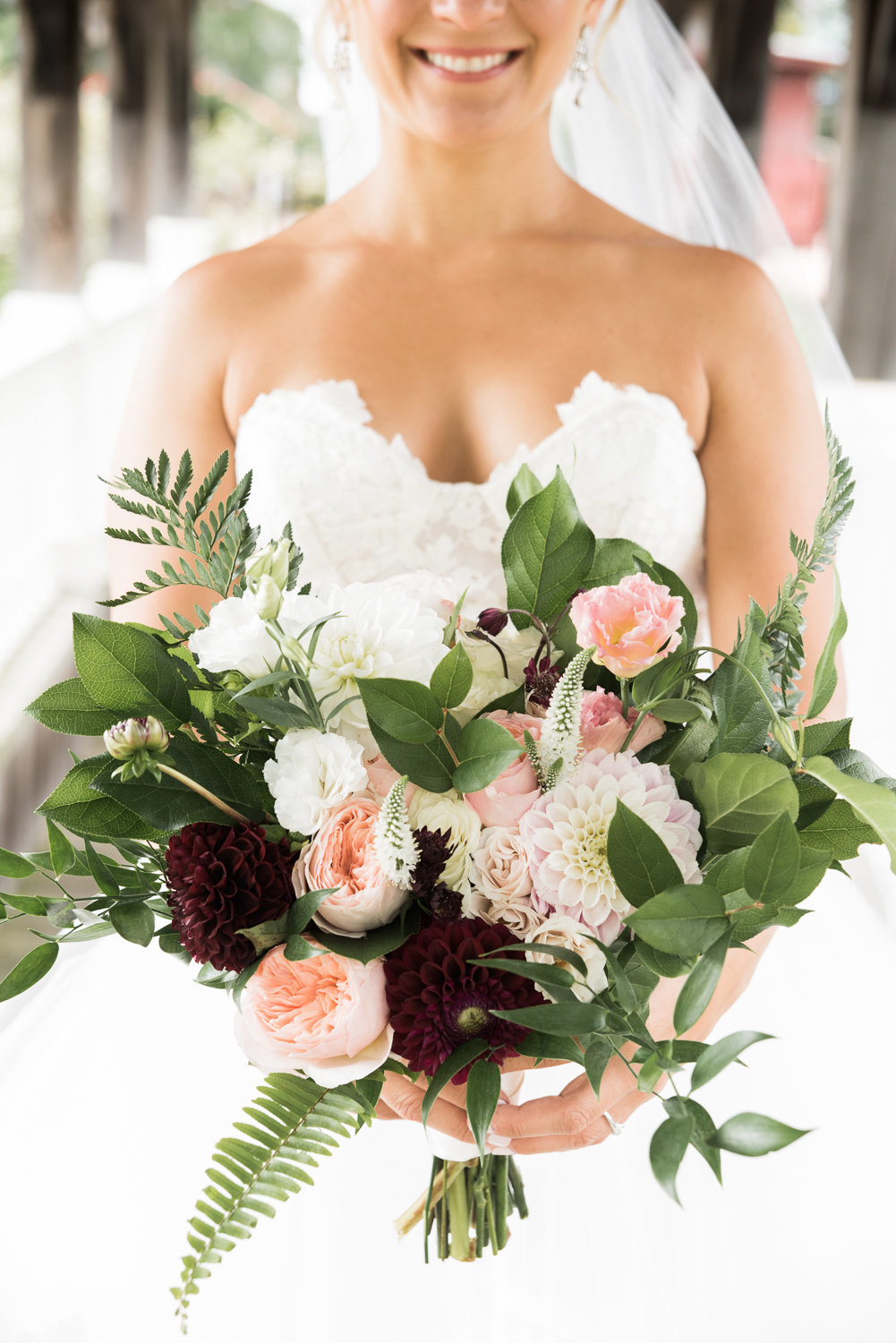 Beautiful, full bridal bouquet with greenery, pinks, and burgundy